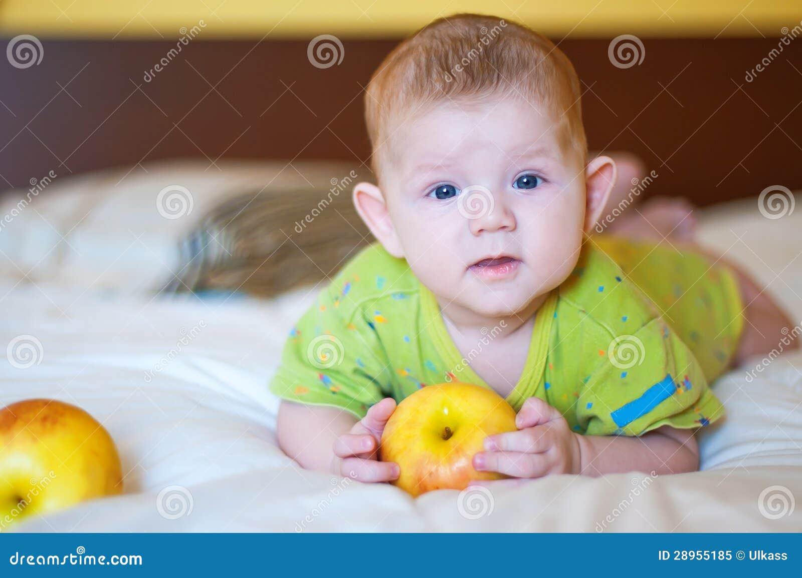 Dziecka mienie i lying on the beach żółty jabłko