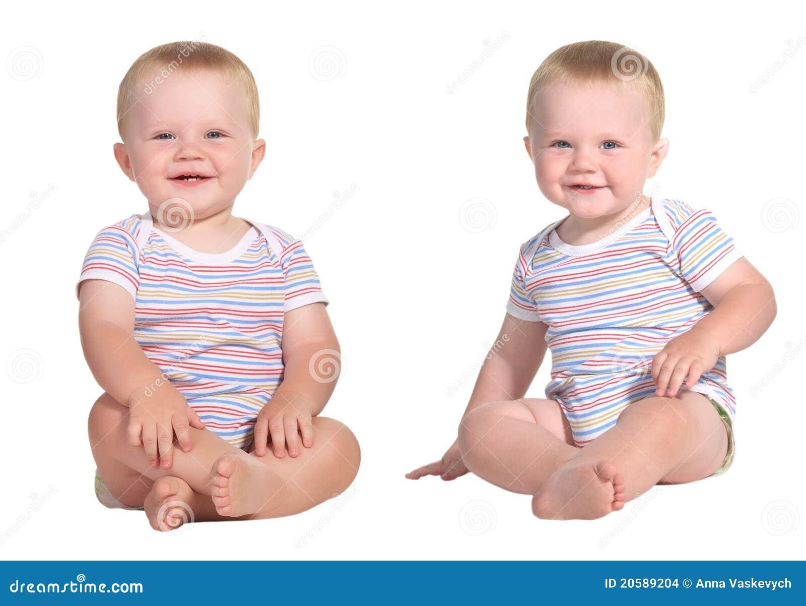 Dziecka obsiadania uśmiechnięci bliźniacy