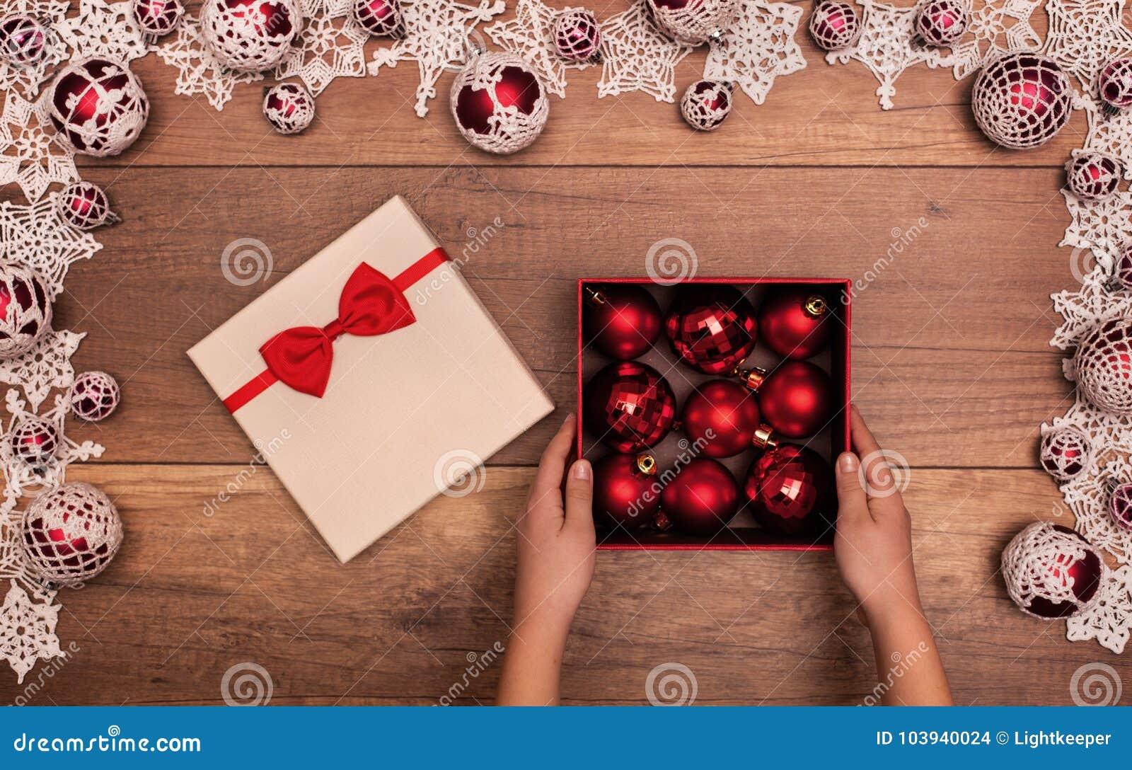 Dziecka otwarcia bożych narodzeń teraźniejszość z czerwonymi baubles