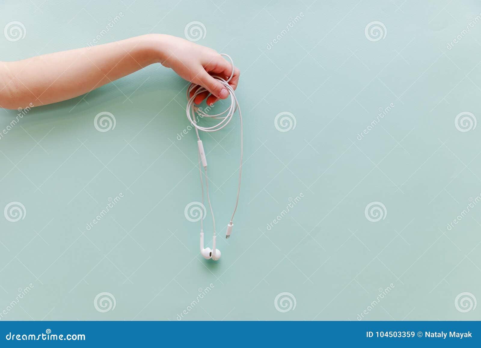 Dziecka ` s ręka utrzymuje hełmofony na błękitnym tle