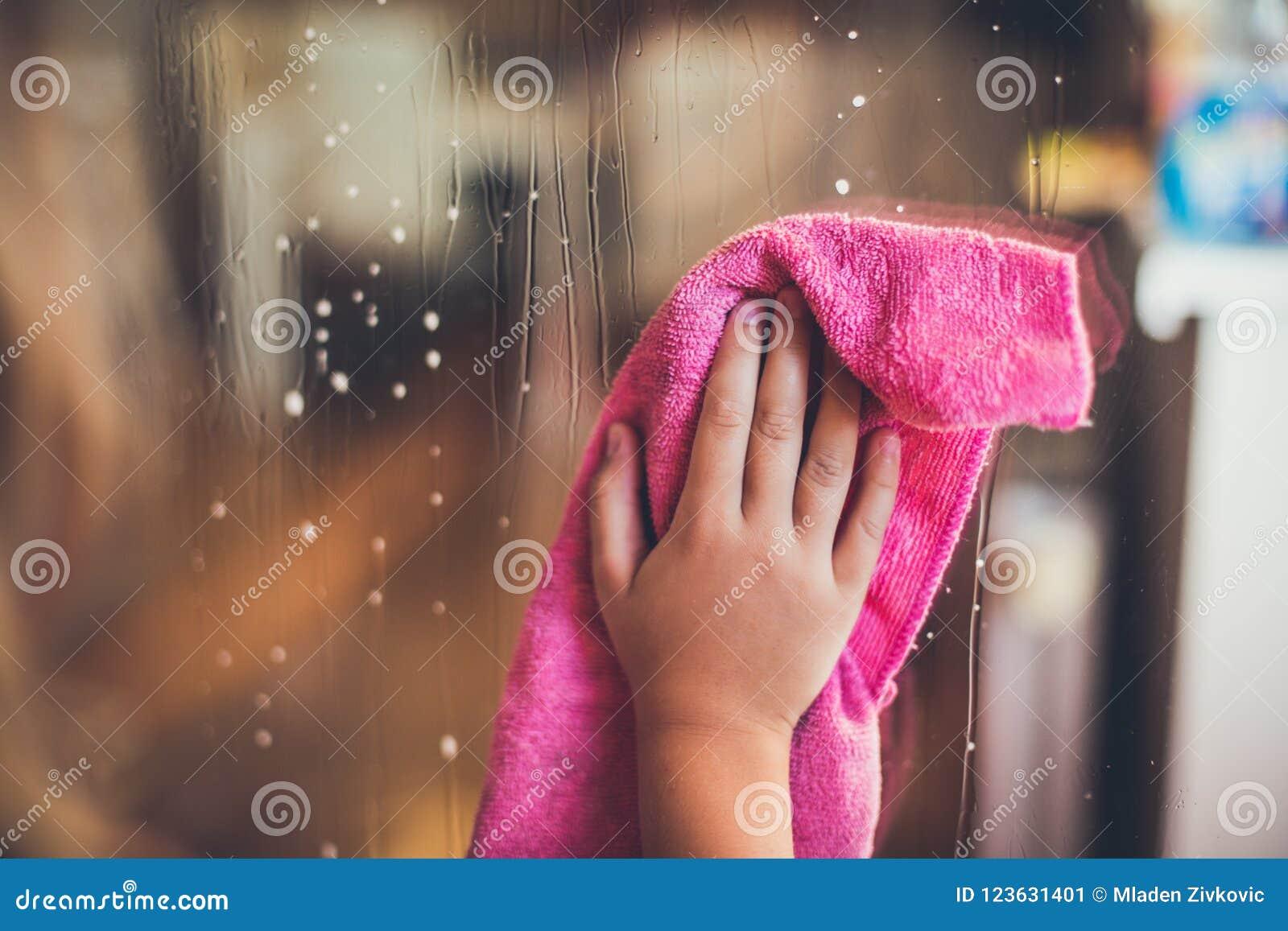 Dziecka ` s ręka wyciera okno