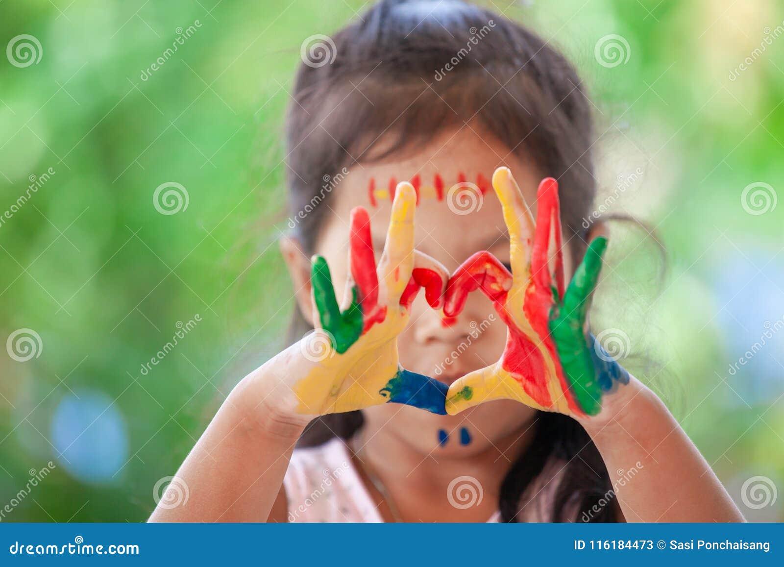 Dziecka ` s ręka z malującą kolorową akwarelą robi kierowemu kształtowi