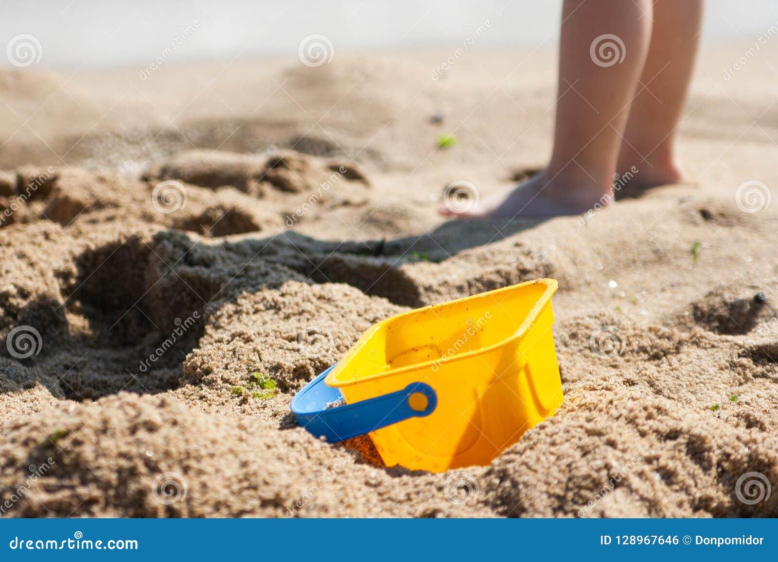 Dziecka wiadro na piaskowatej plaży w tle