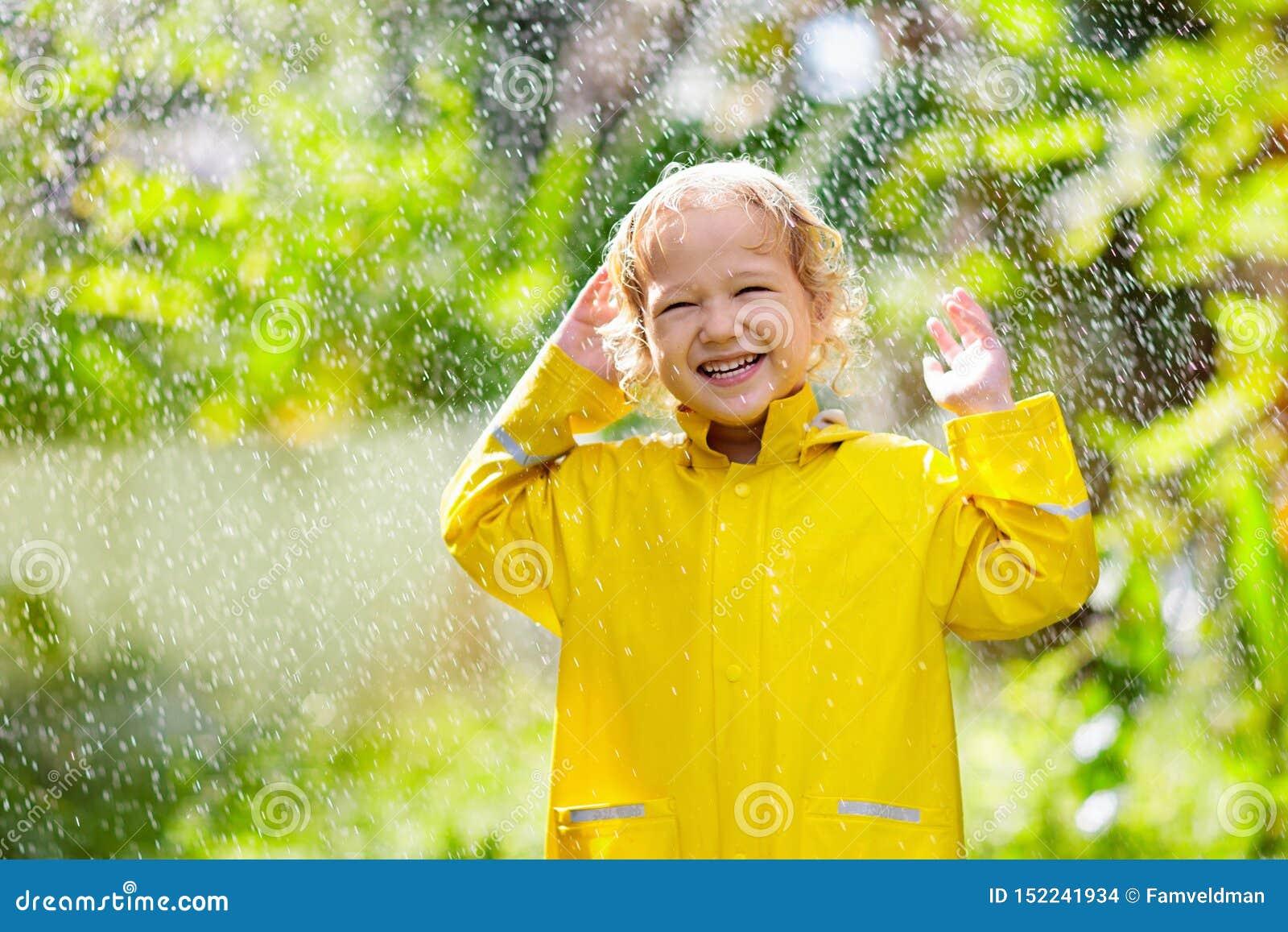 Dziecko bawi? si? w deszczu Dzieciak z parasolem
