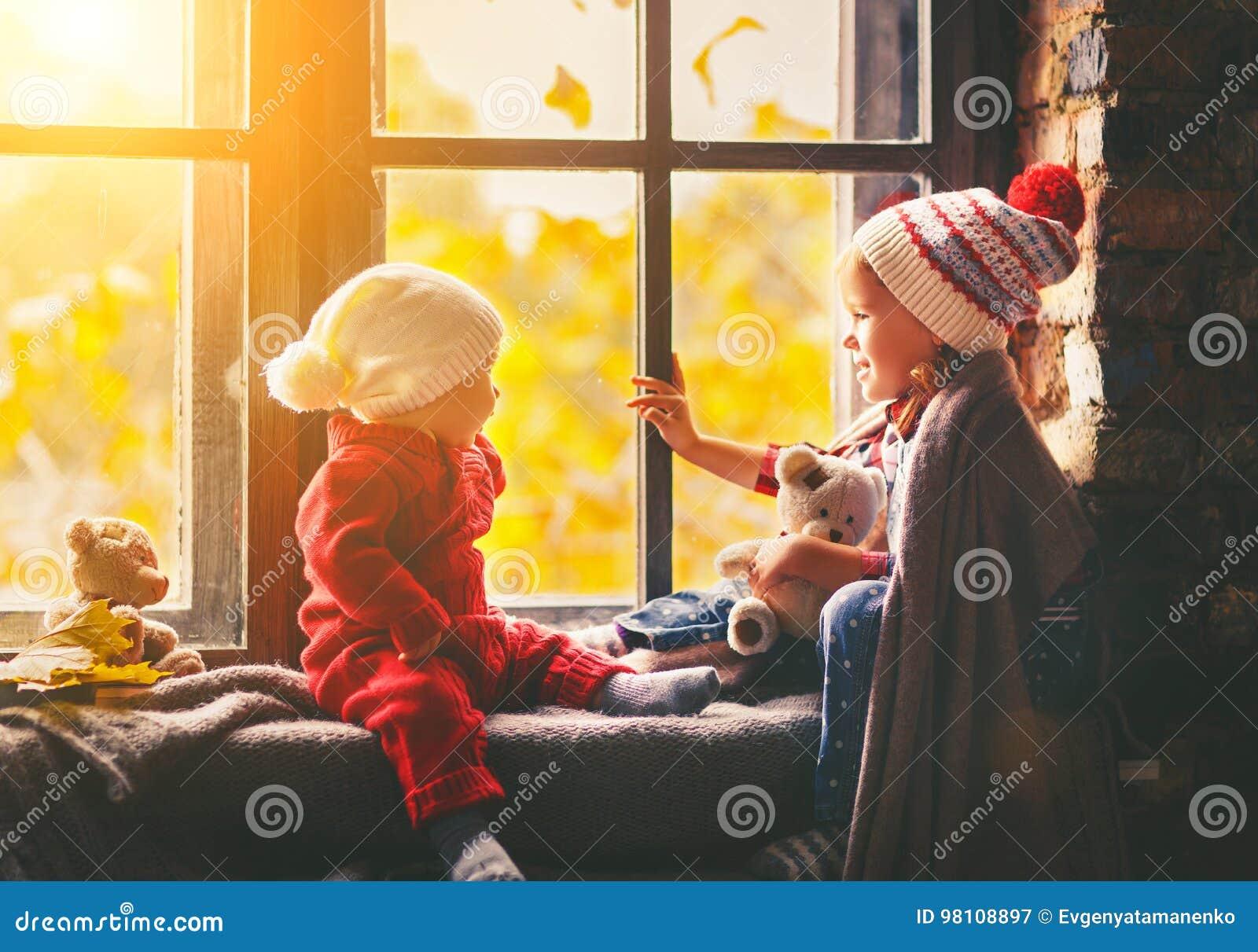 Dziecko brat i siostrzany podziwia okno dla jesieni