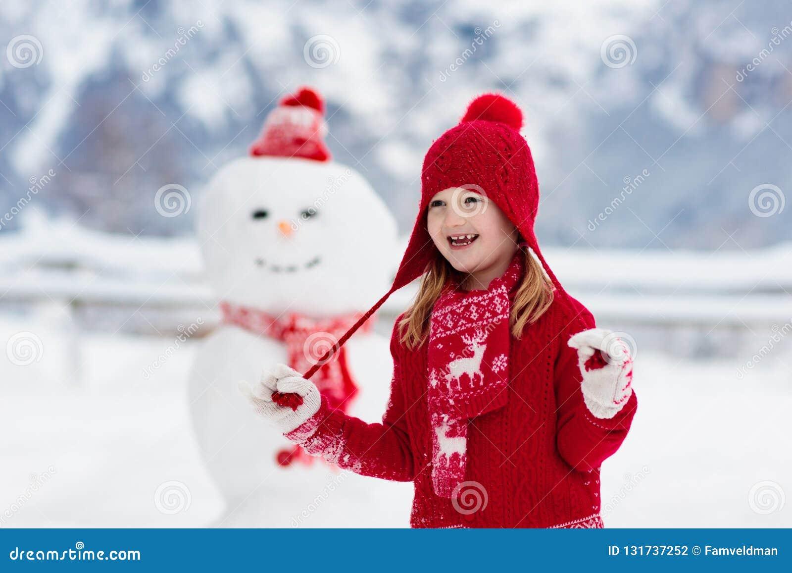 Dziecko budynku bałwan Dzieciak budowy śnieżny mężczyzna Chłopiec i dziewczyna bawić się outdoors na śnieżnym zima dniu