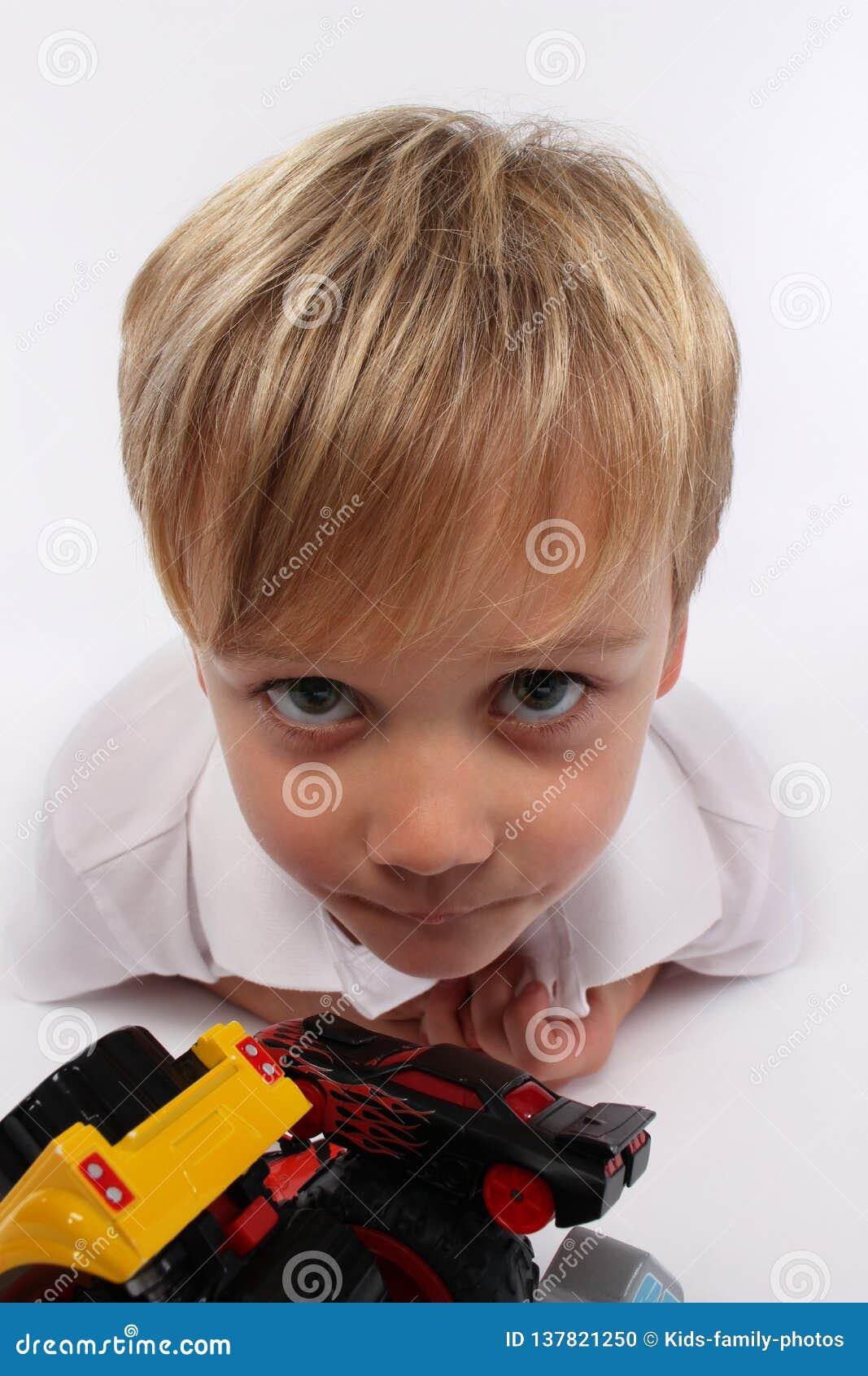 Dziecko chłopiec robi niemądrym twarzom i chce ciebie bawić się