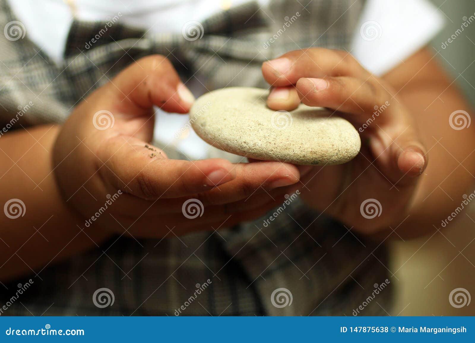 Dziecko dotyka trzymaj?cy bielu kamie? R?ki 1 roczniaka dziecko
