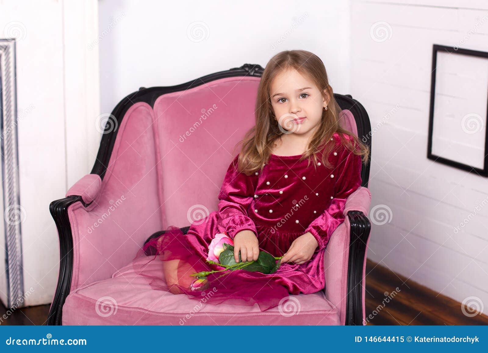 Dziecko dziewczyna jest piękna, śliczna, rozochocona i szczęśliwa na różowym karle w modnej luksusowej sukni, szcz??liwy dzieci?s