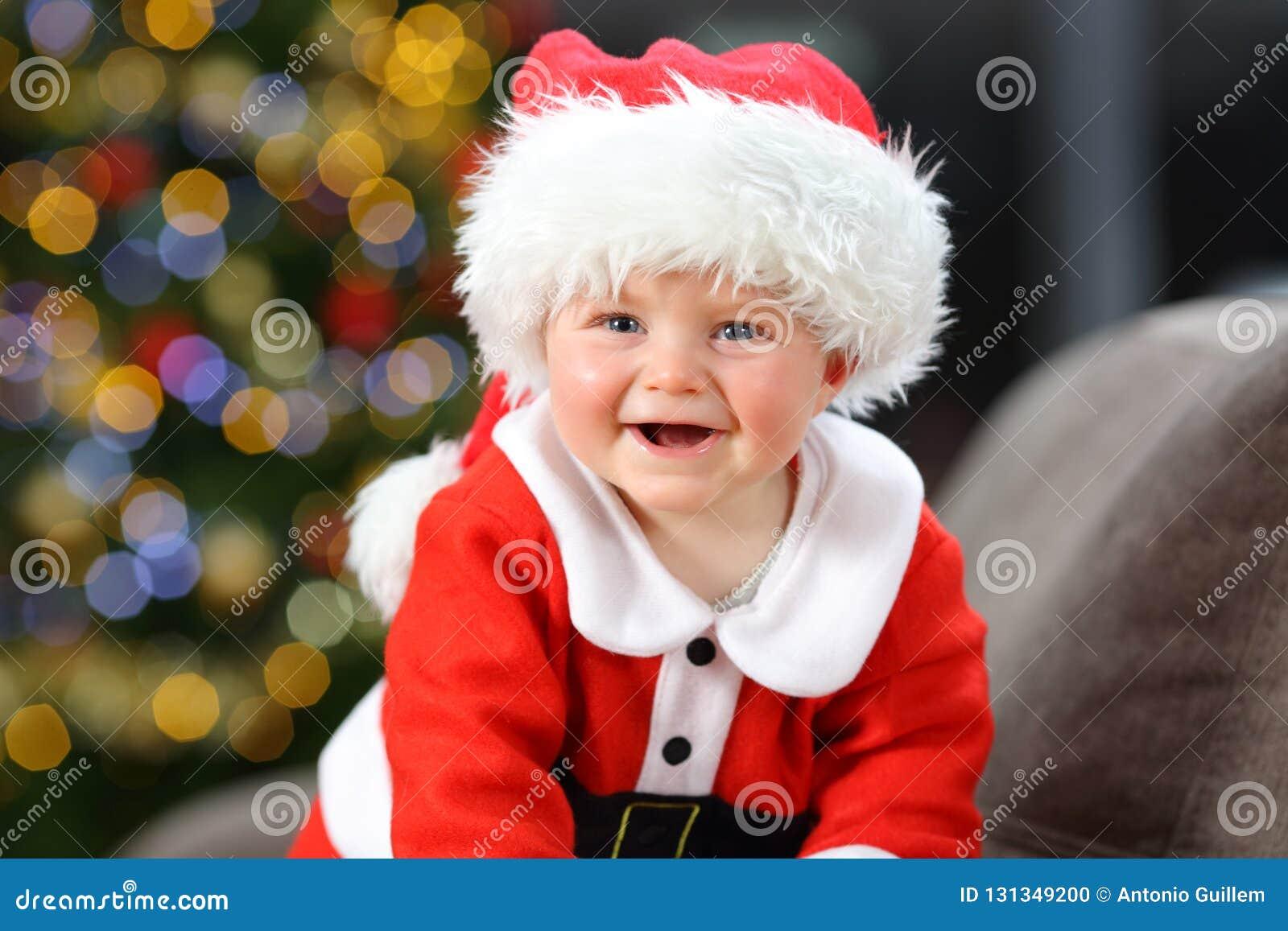 Dziecko jest ubranym Santa przebranie patrzeje kamerę w bożych narodzeniach