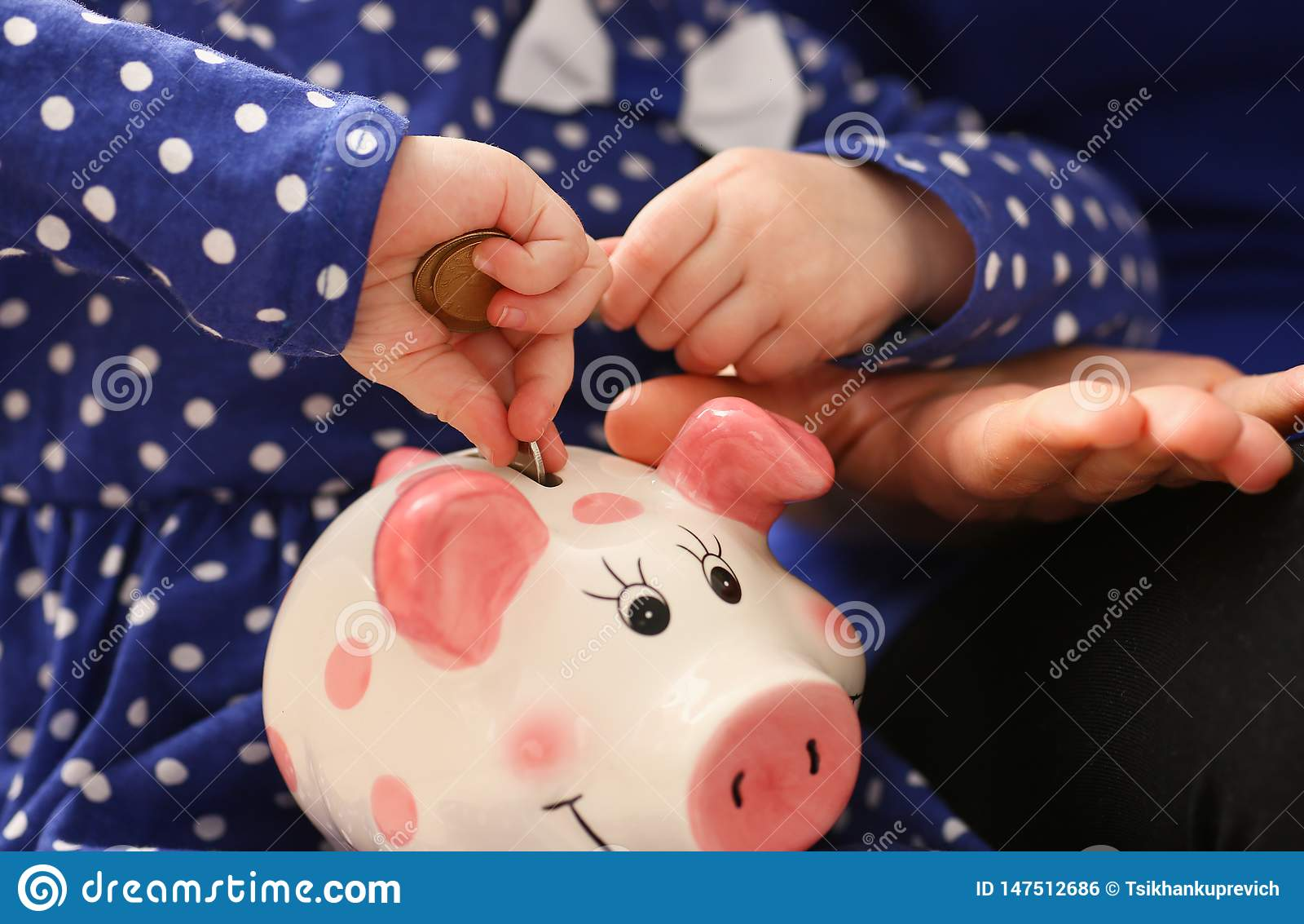 Dziecko ma?ej dziewczynki r?ki k?adzenia monety w piggybank