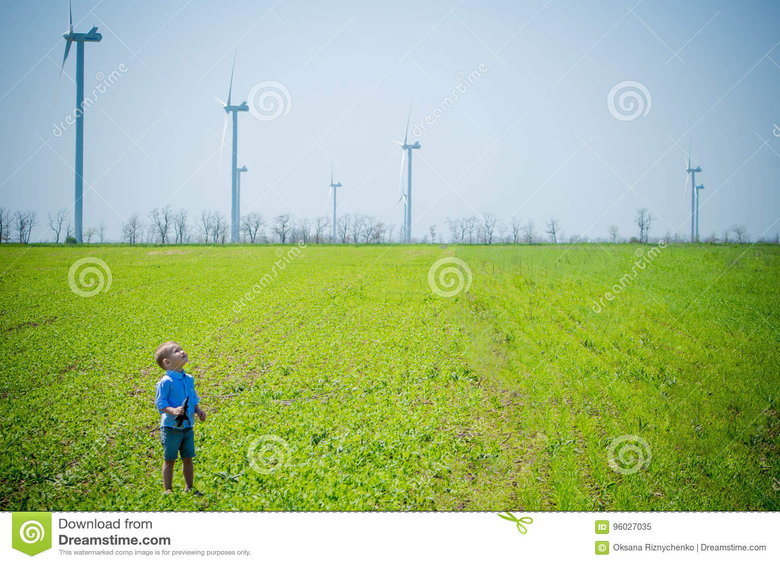 Dziecko na polu z wiatrowymi generatorami