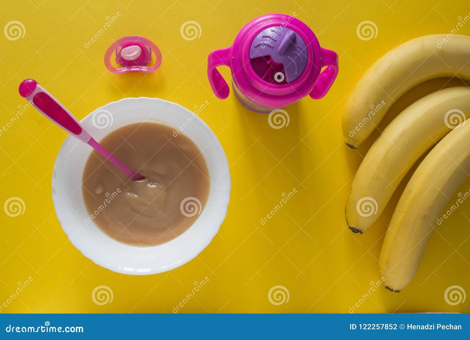 Dziecko owsianka dla dziecka i bananów na koloru żółtego tła bananach