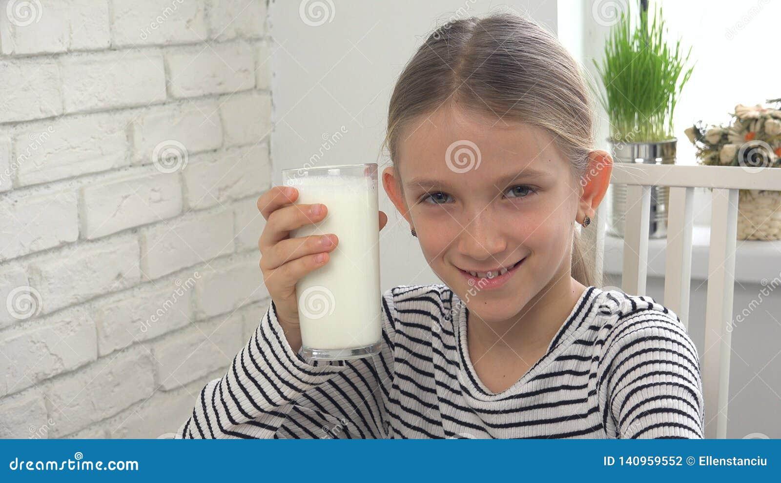 Dziecko Pije mleko przy śniadaniem w kuchni, dziewczyna Smaczni nabiały