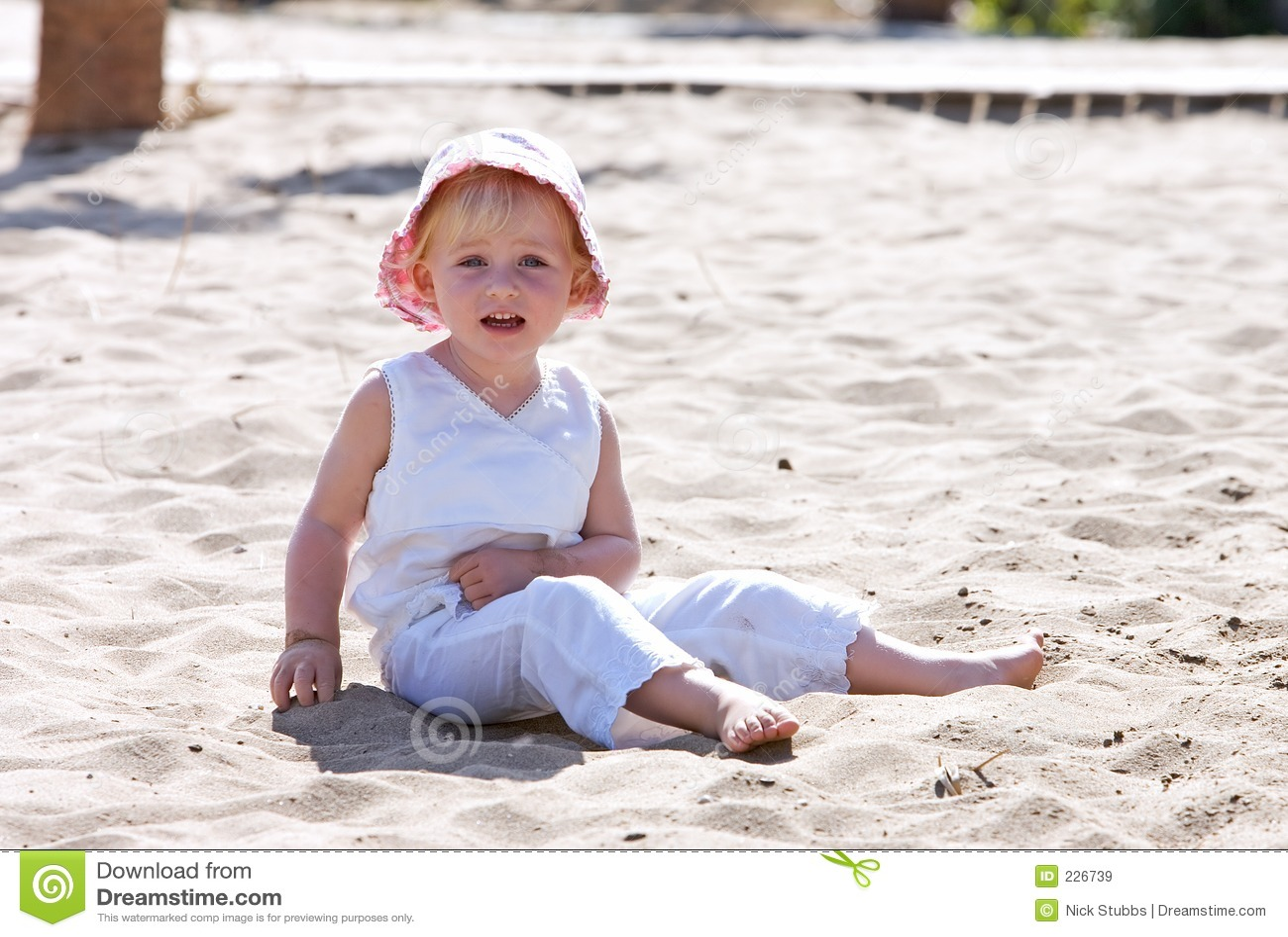 Dziecko plażowych kapeluszu różowego siedzi młody