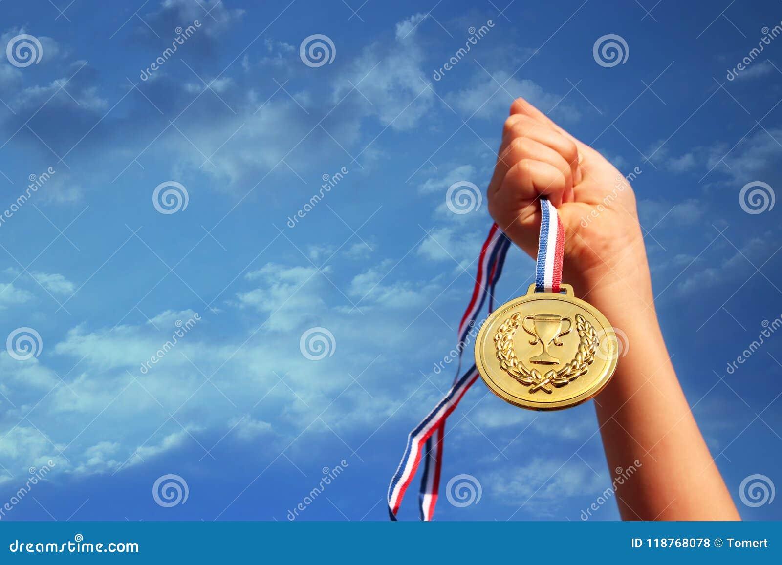 Dziecko ręka podnosząca, trzymający złotego medal przeciw niebu edukaci, sukcesu, osiągnięcia, nagrody i zwycięstwa pojęcie,