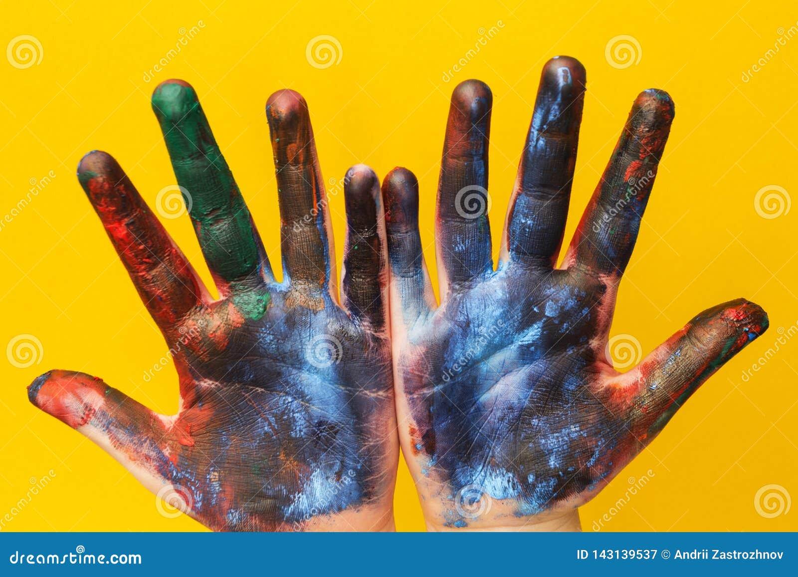 Dziecko ręki plamią z stubarwną farbą na żółtym tle