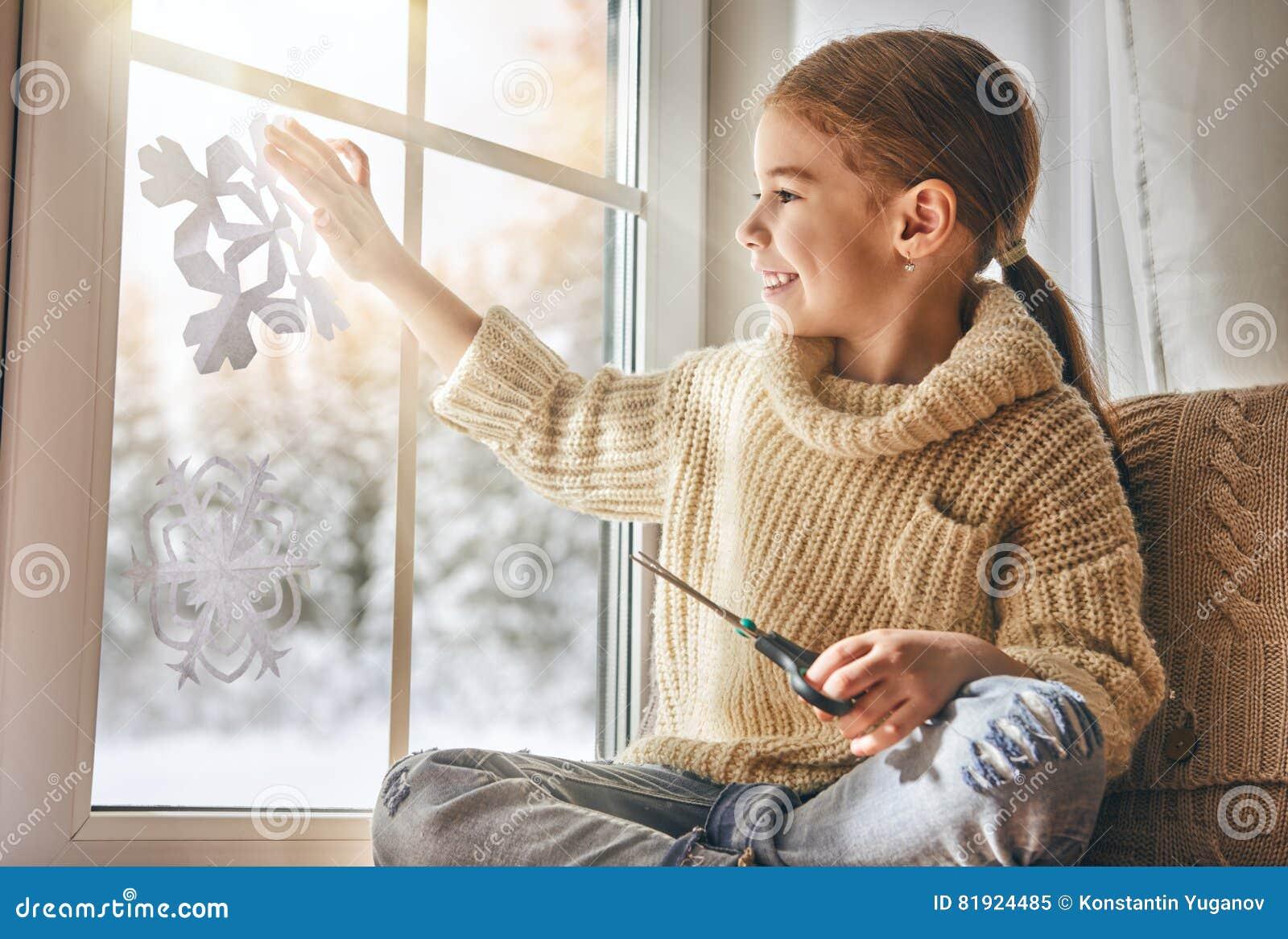 Dziecko robi papierowym płatkom śniegu