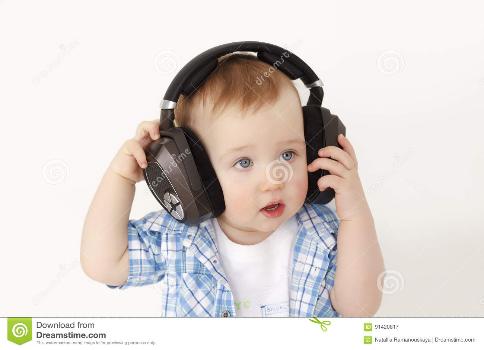 Dziecko słucha muzyka w wielkich hełmofonach