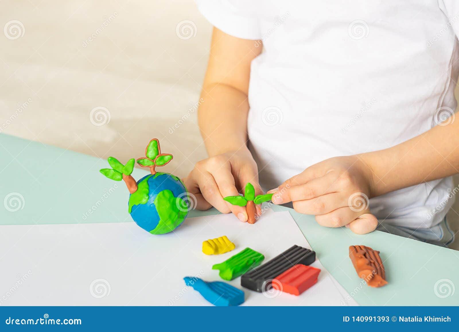 Dziecko sculpts od plasteliny drzewa i kulę ziemską Układ planeta w dziecko palmach Pojęcie ekologia