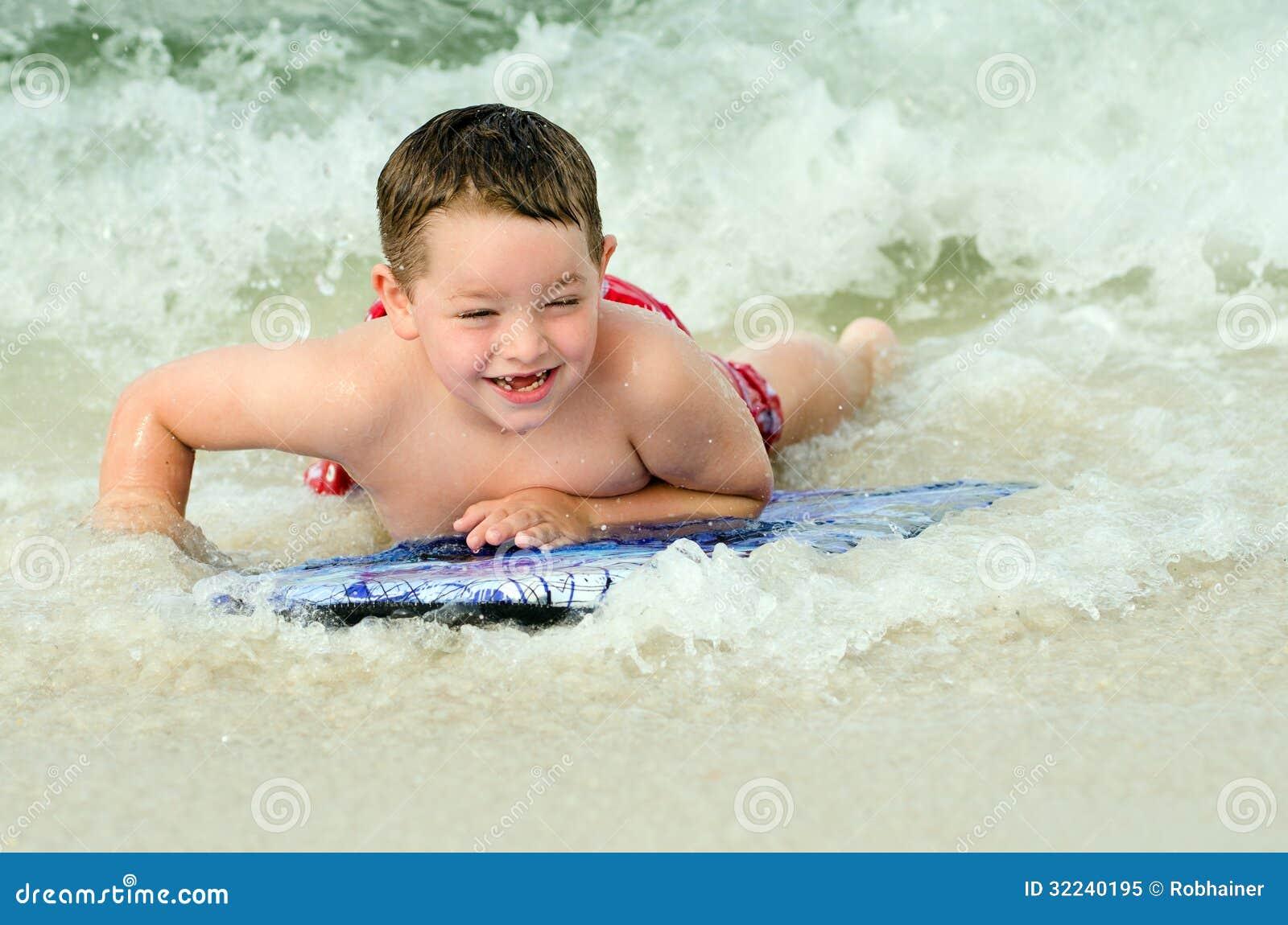Dziecko surfing na bodyboard przy plażą