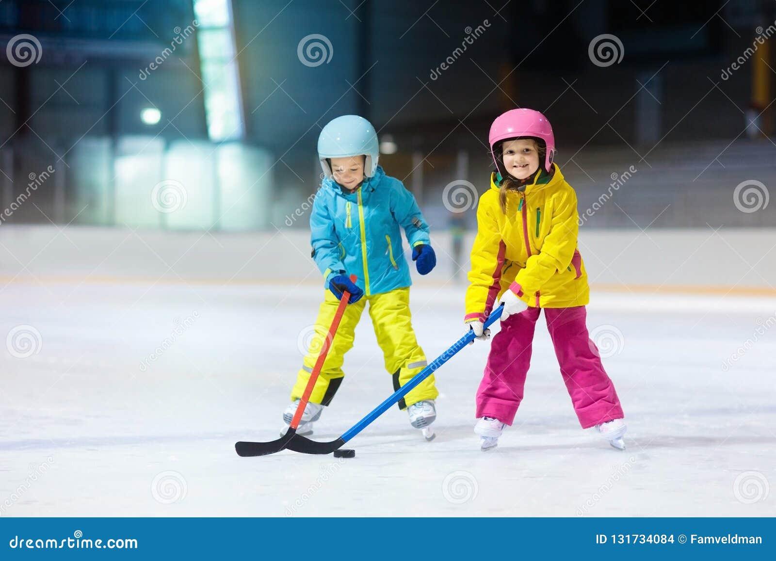 Dziecko sztuki lodowy hokej na salowym lodowisku Zdrowy zima sport dla dzieciaków Chłopiec i dziewczyna z hokejowymi kijami uderz