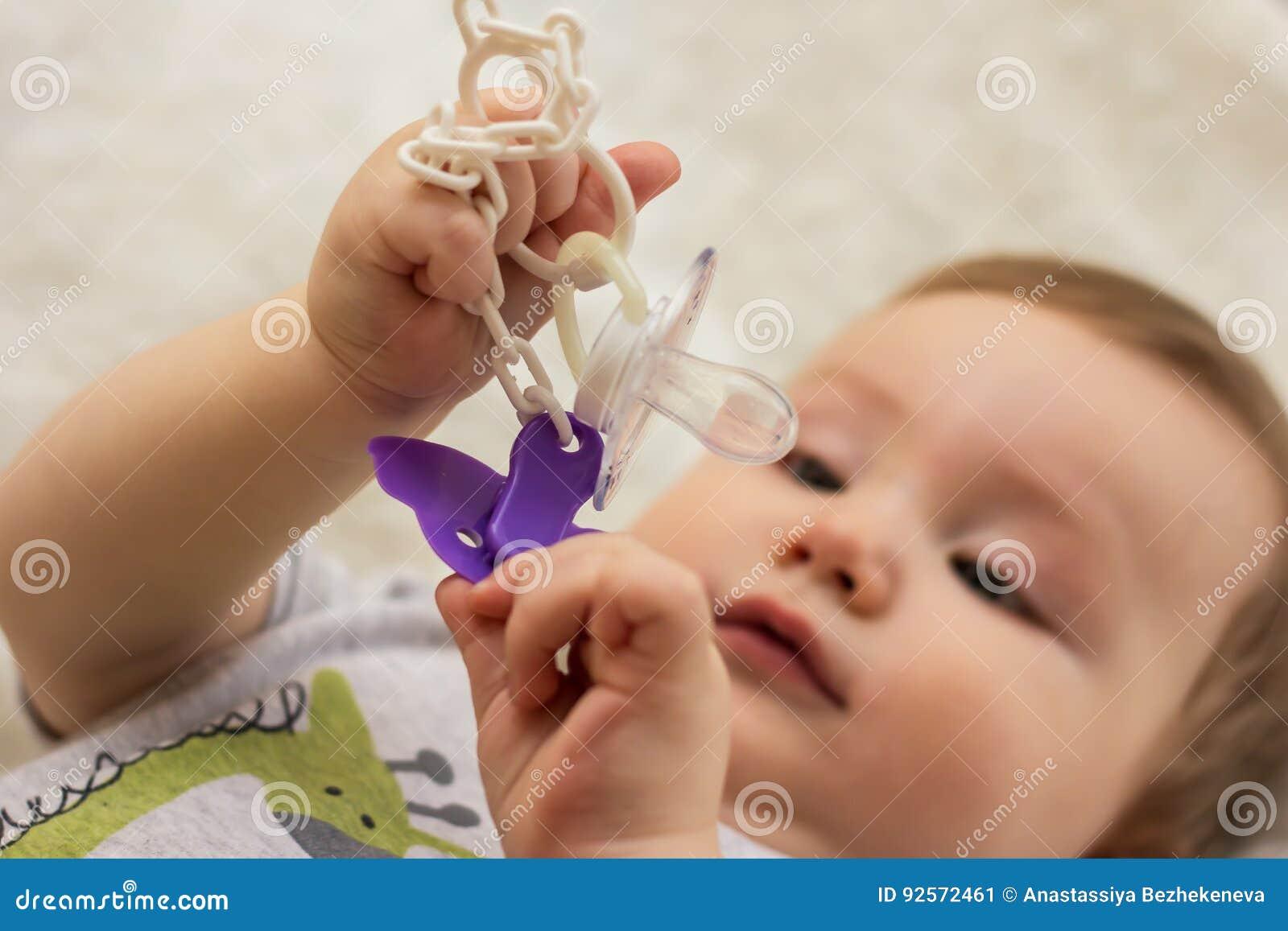 Dziecko trzyma pacyfikator klamerkę dla sutka