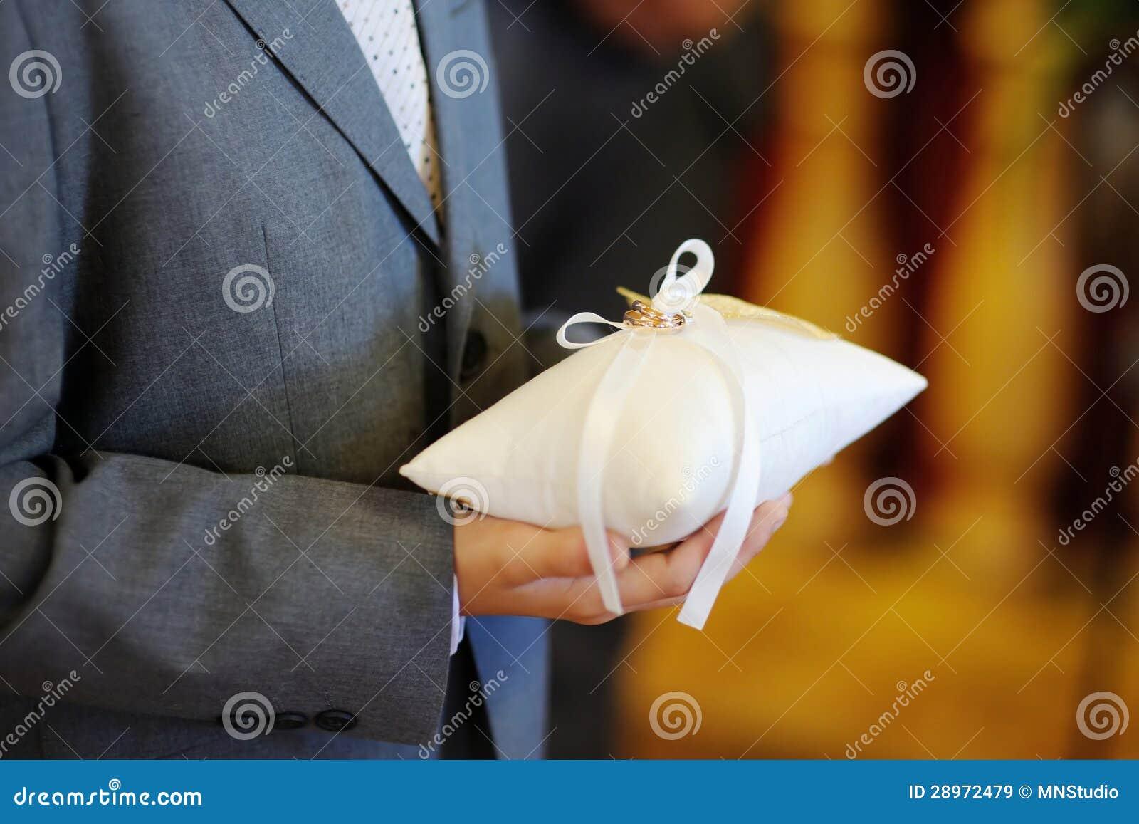 Dziecko trzyma poduszkę z obrączkami ślubnymi