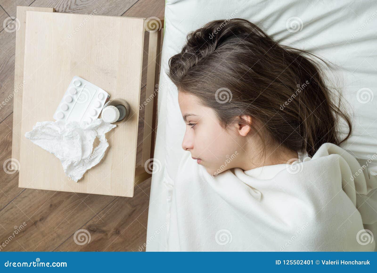 Dziecko w łóżku w domu łapał zimno, bierze medycyny, grypowy sezon