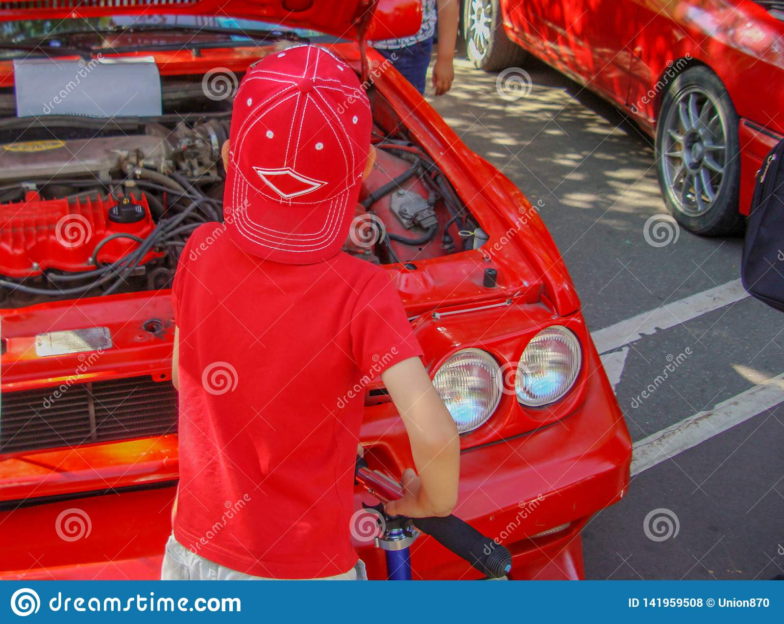 Dziecko w czerwieni ubraniach egzamininuje silnika samochód