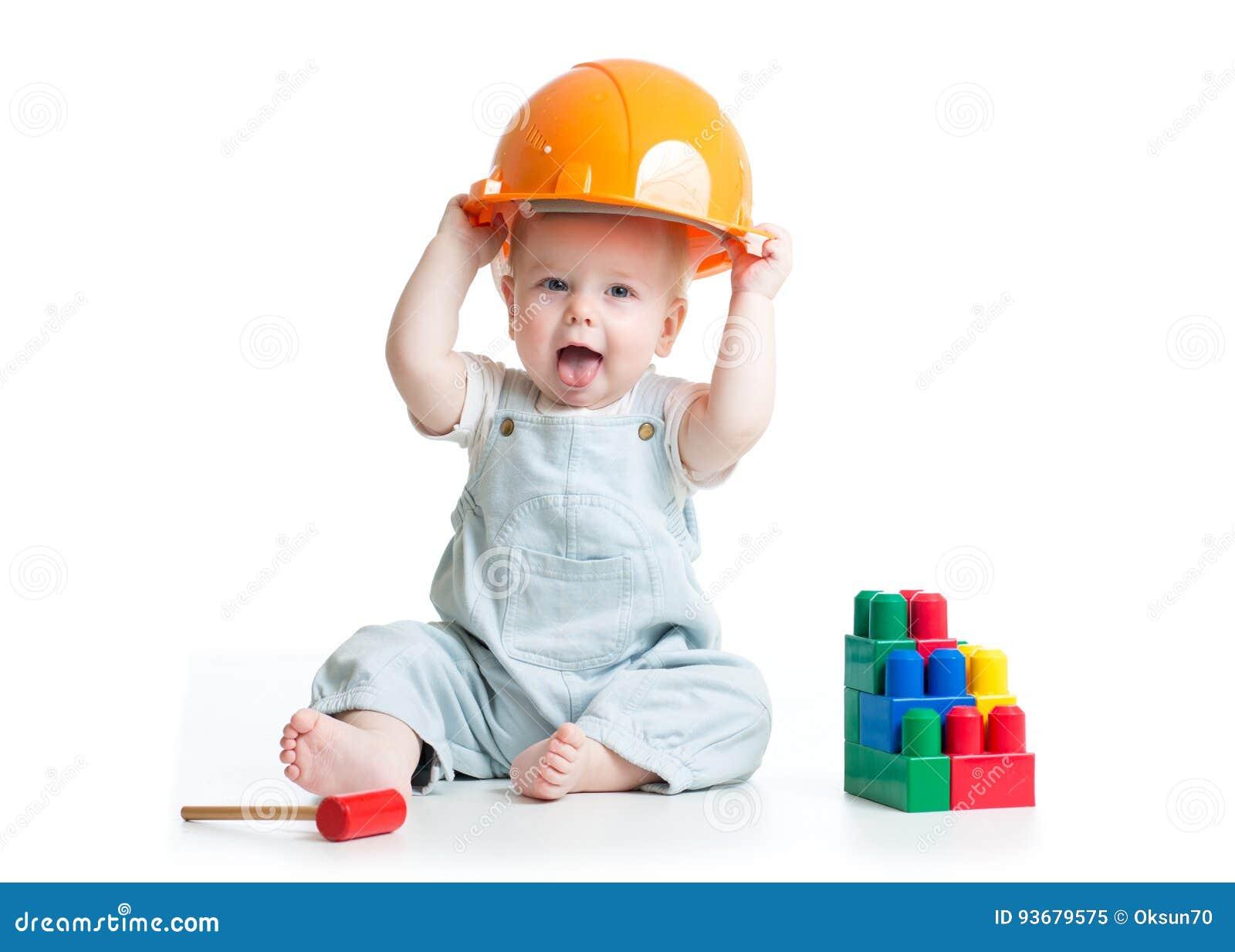 Dziecko w hardhat bawić się zabawki odizolowywać na białym tle