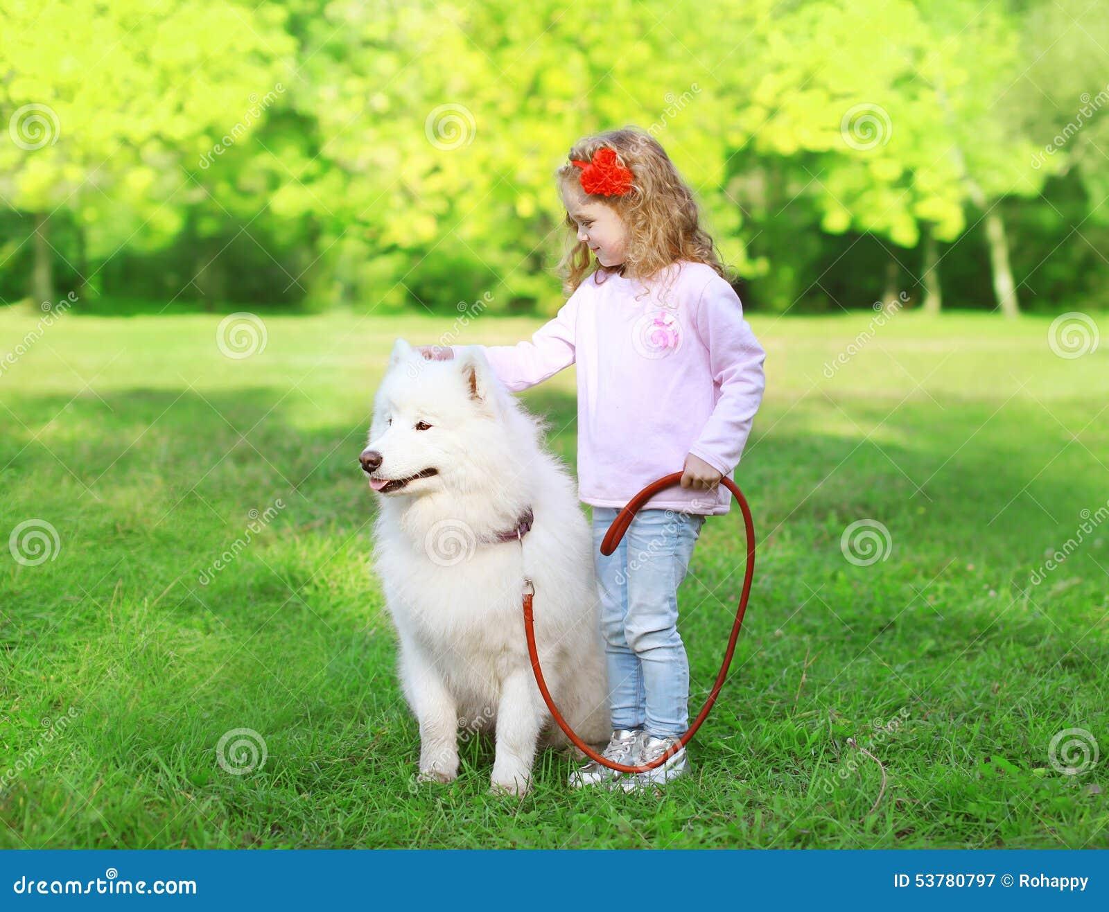 Dziecko z białym Samoyed psem na gras