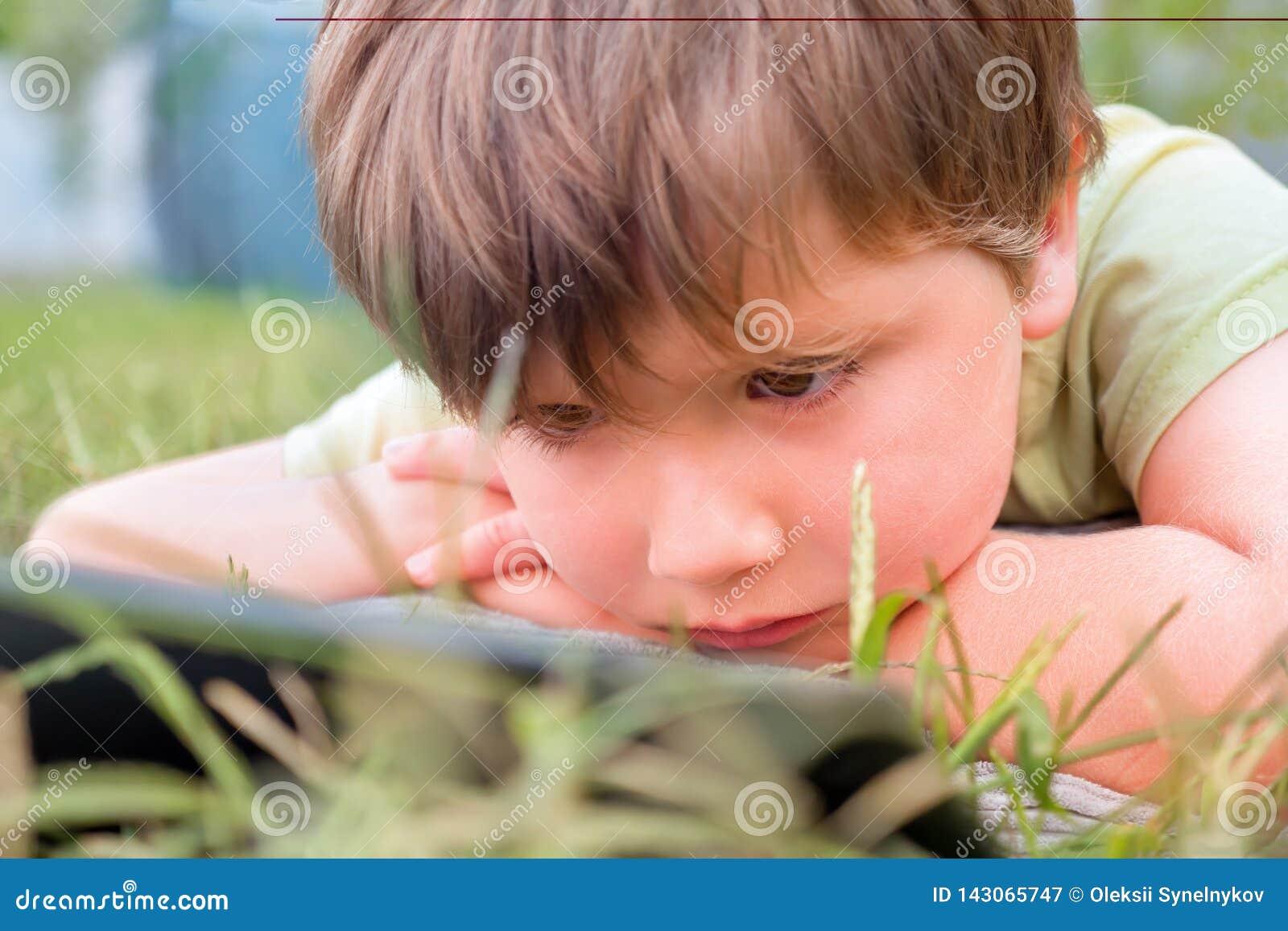 Dziecko z ipad na zielonej trawie Portret chłopiec z pastylką Oko problemy powodować używać pastylki zbyt dużo ręk opieki zdrowie