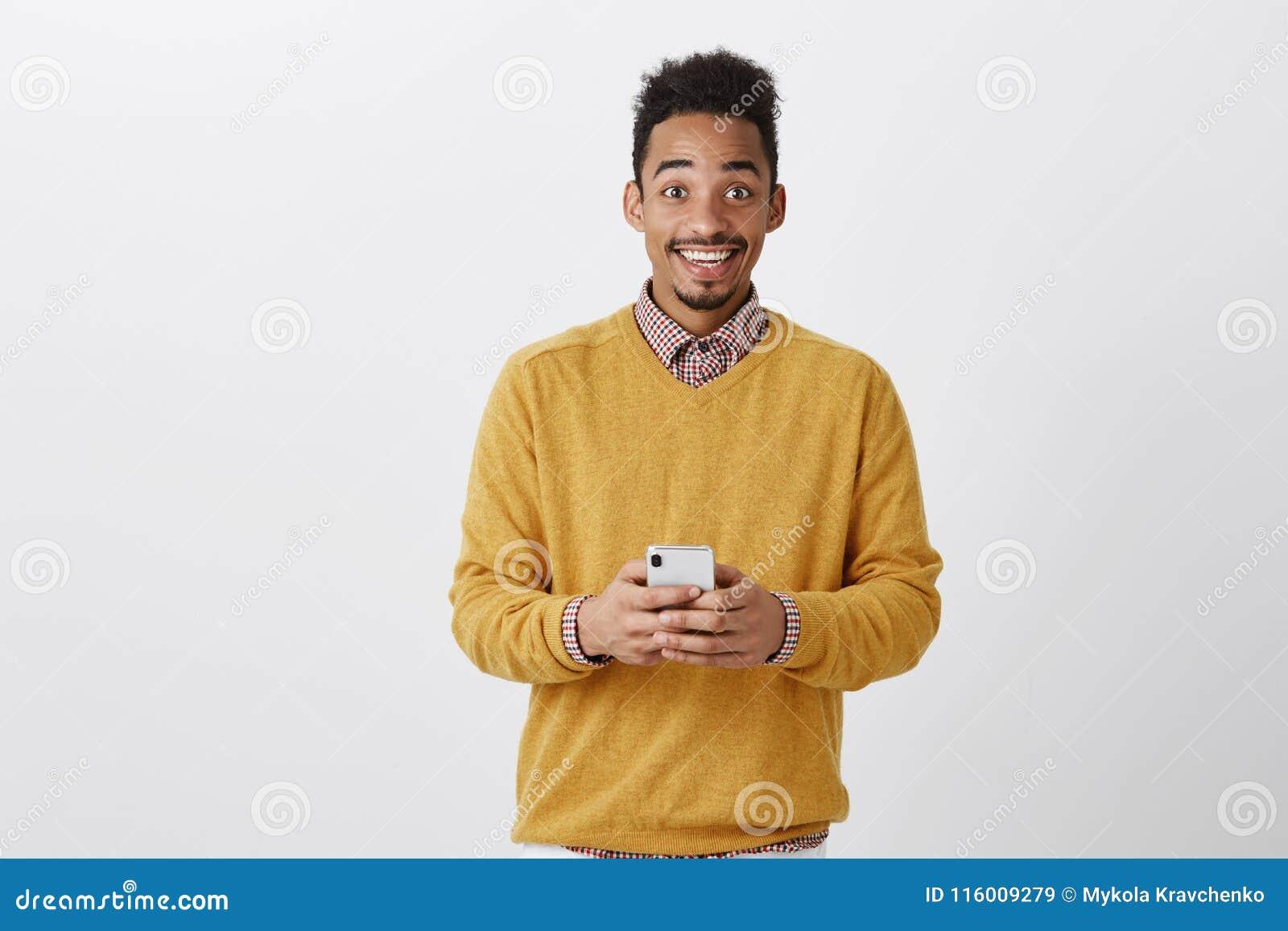 Dzielić wielką wiadomość z przyjacielem Portret szczęśliwy wstrząśnięty ciemnoskóry mężczyzna w modnym stroju, trzymający smartph