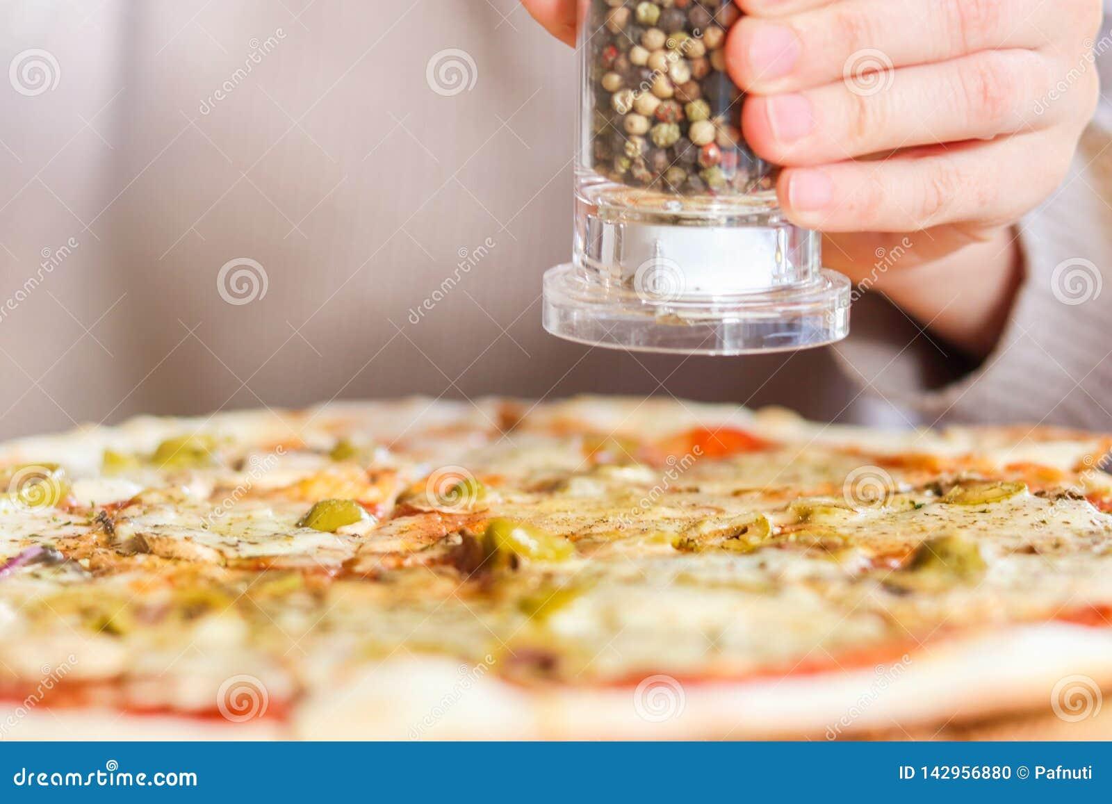 Dziewczyn sumujące pikantność na górze pizzy