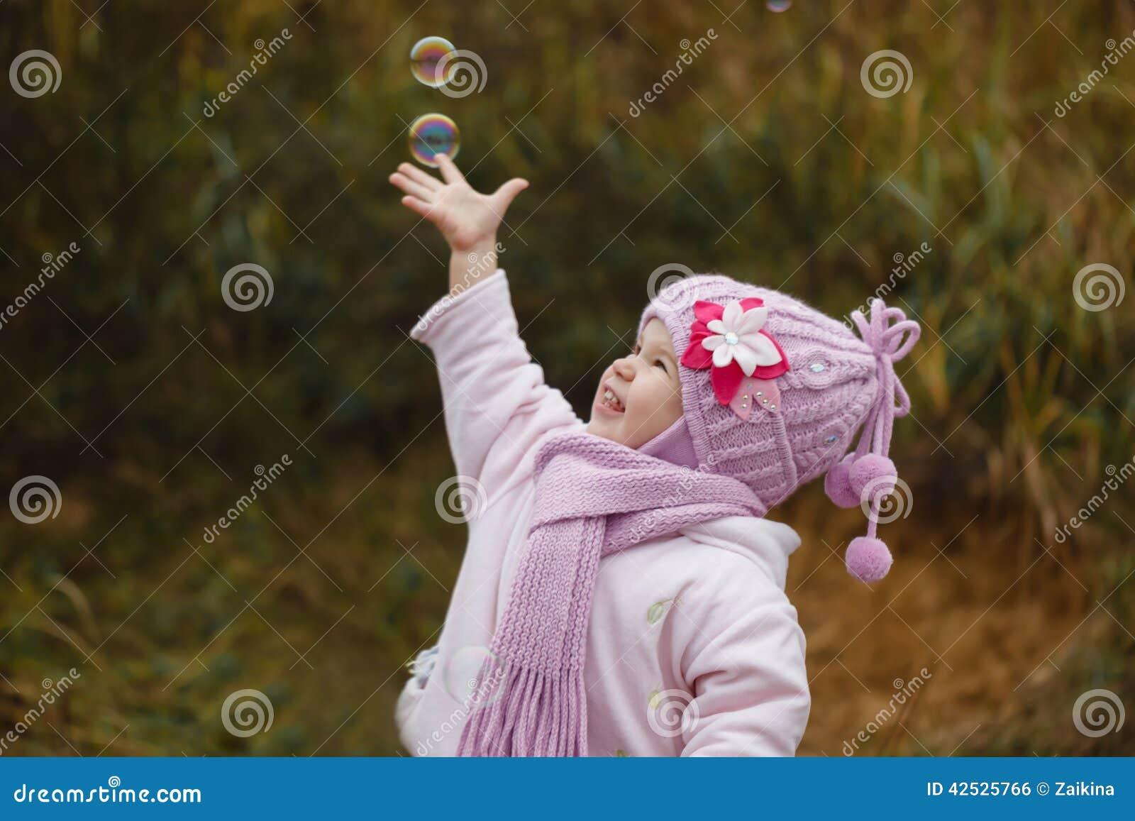 Dziewczyna łapie mydlanych bąble w jesieni