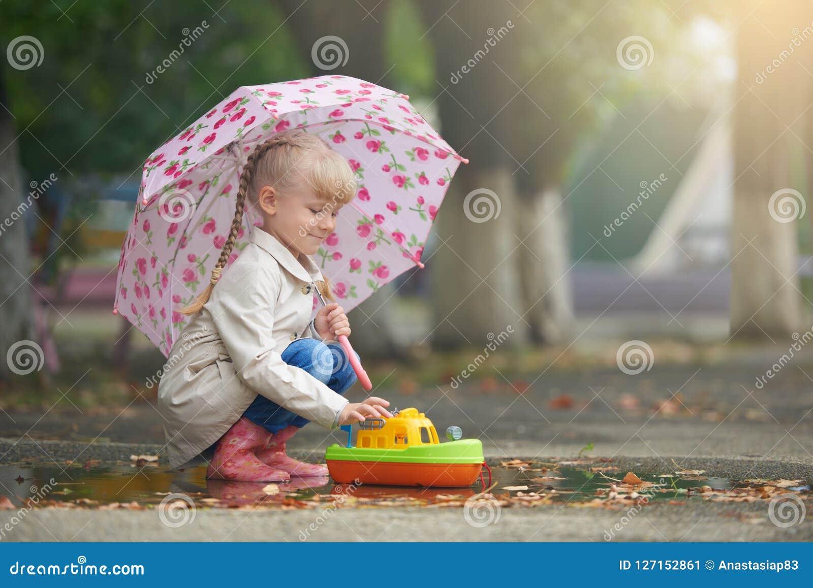 Dziewczyna bawić się w kałuży z łodzią po deszczu