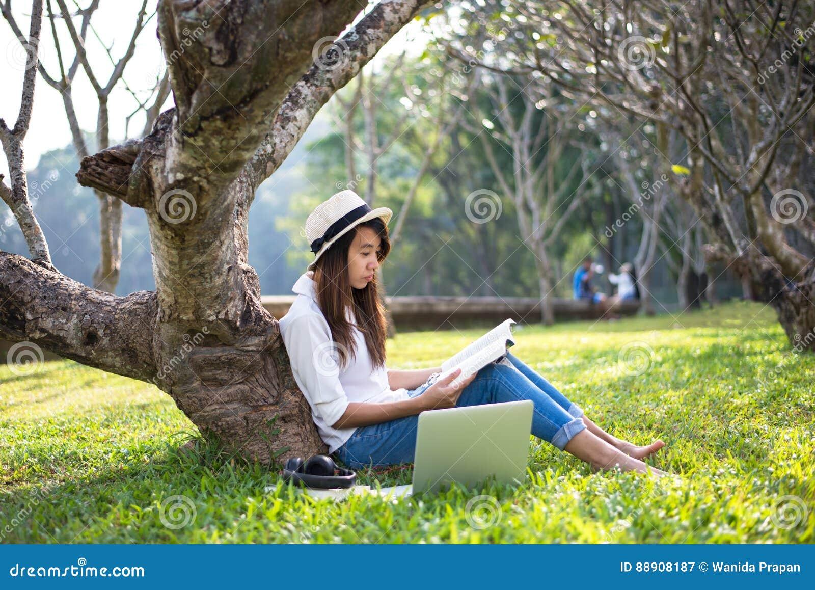Dziewczyna cieszy się czytający książkę pod drzewem, kłaść na trawie park