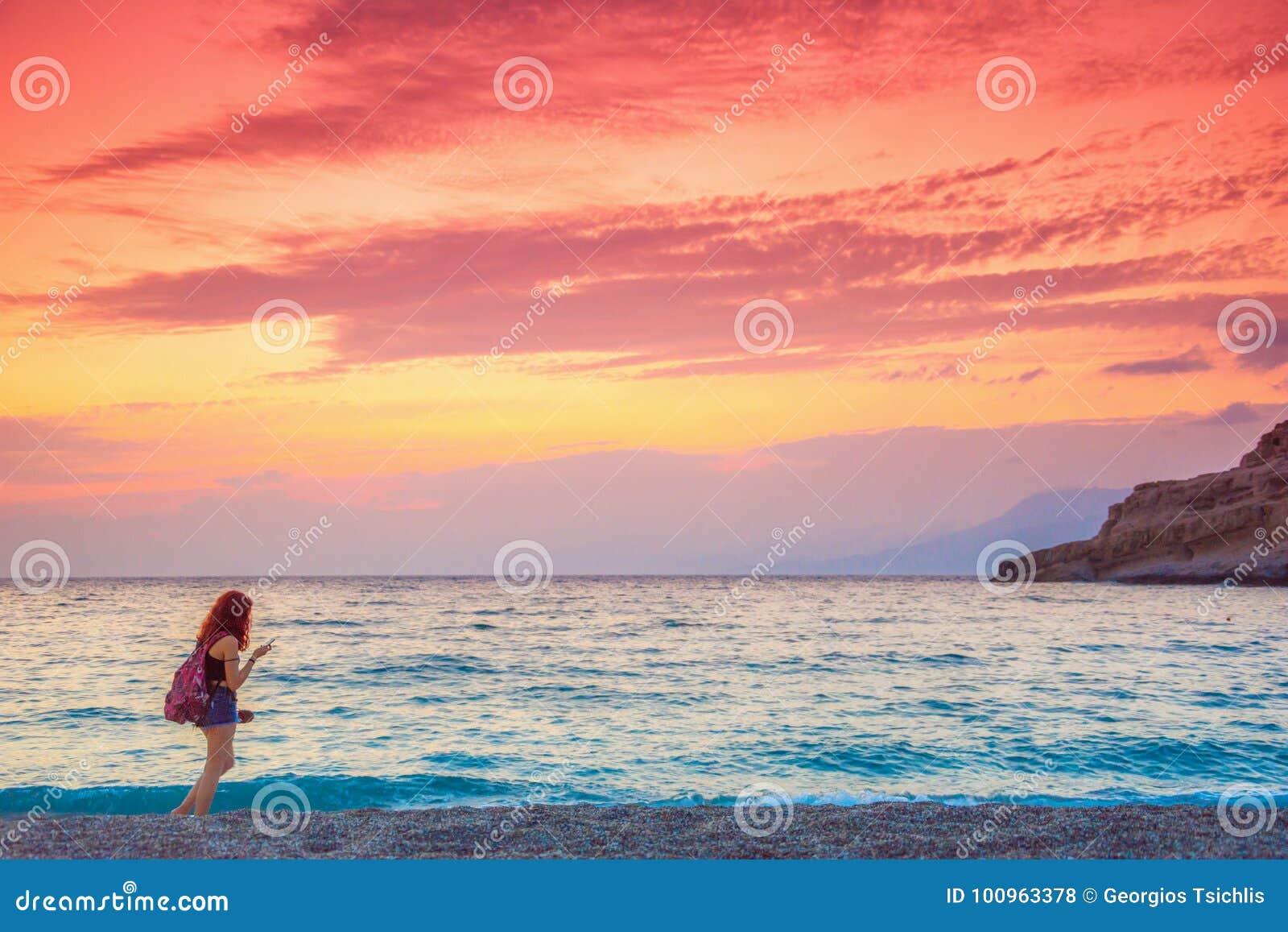 Dziewczyna cieszy się zadziwiającego zmierzch przy plażą Matala