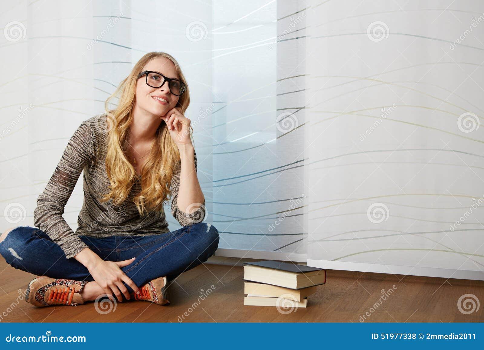 Dziewczyna czyta książkowego obsiadanie na podłoga