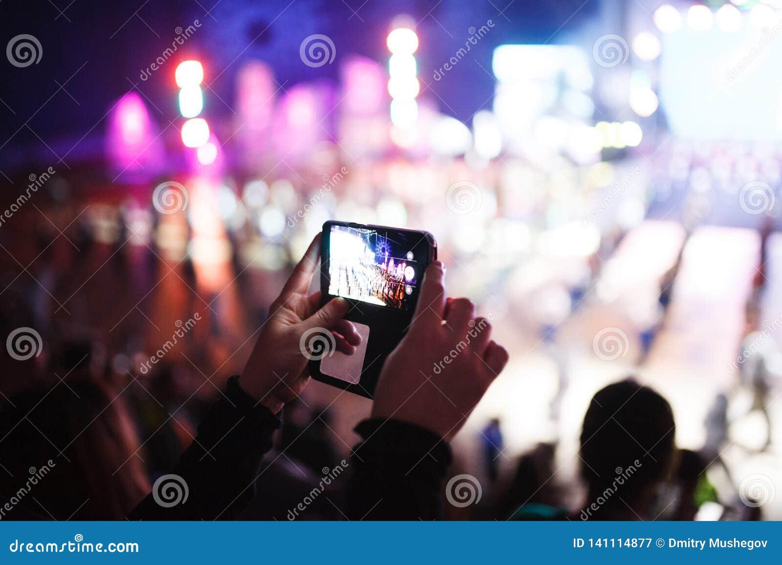 Dziewczyna fotografuje jaskrawego wydarzenie na jej smartphone