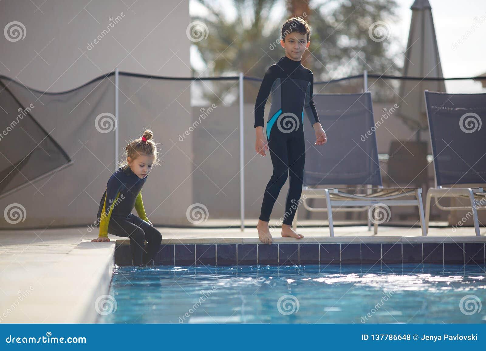 Dziewczyna i chłopiec przygotowywamy skakać w basen