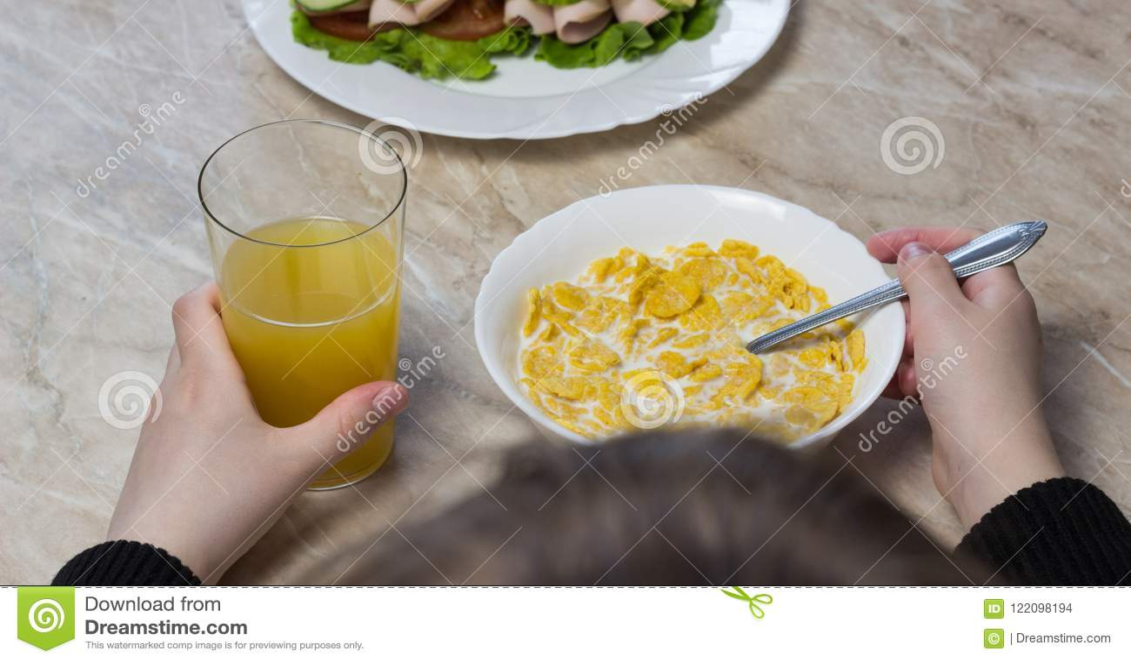 Dziewczyna je cornflakes z mlekiem przed szkolną uczennicą