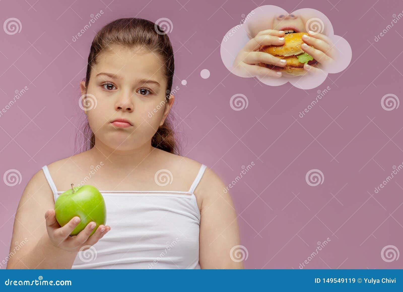 Dziewczyna je zielonego Apple ale marzy o hamburgerze, Harmonijny i zdrowy jedzenie dla dzieci Dziecko je zdrow? przek?sk?