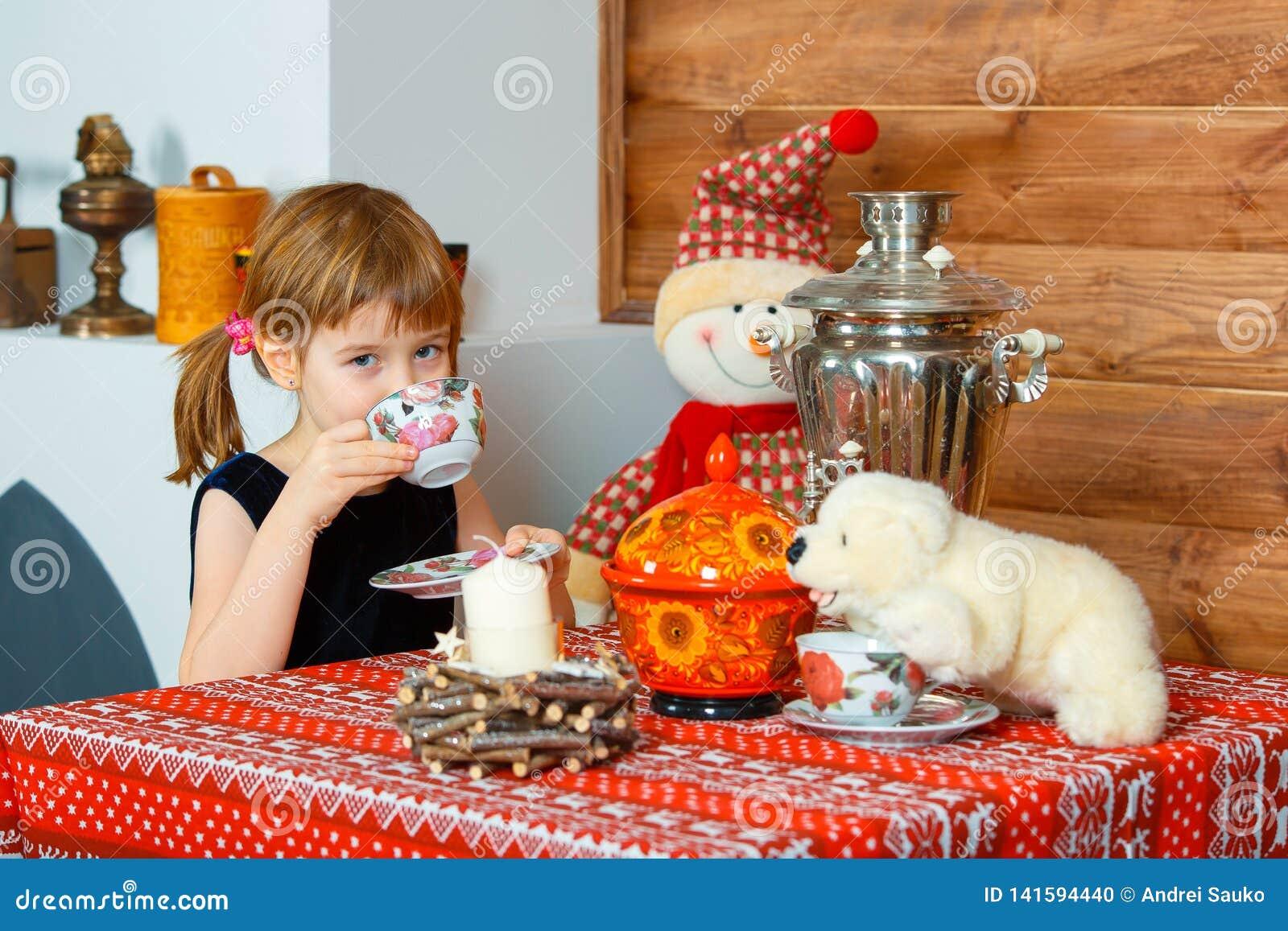 Dziewczyna jest pić herbaciany i uśmiechnięty