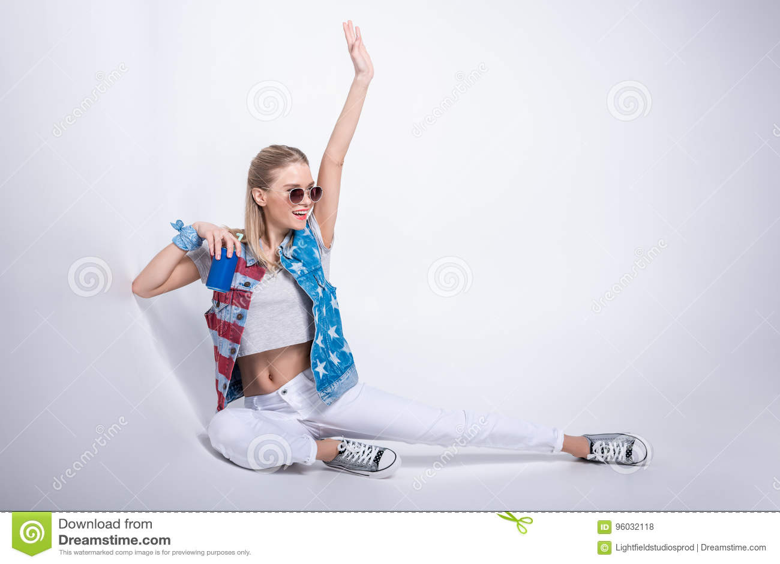 Dziewczyna jest ubranym drelichową kamizelkę z i pije sodę od aluminiowej puszki w okularach przeciwsłonecznych gwiazdami i lampa