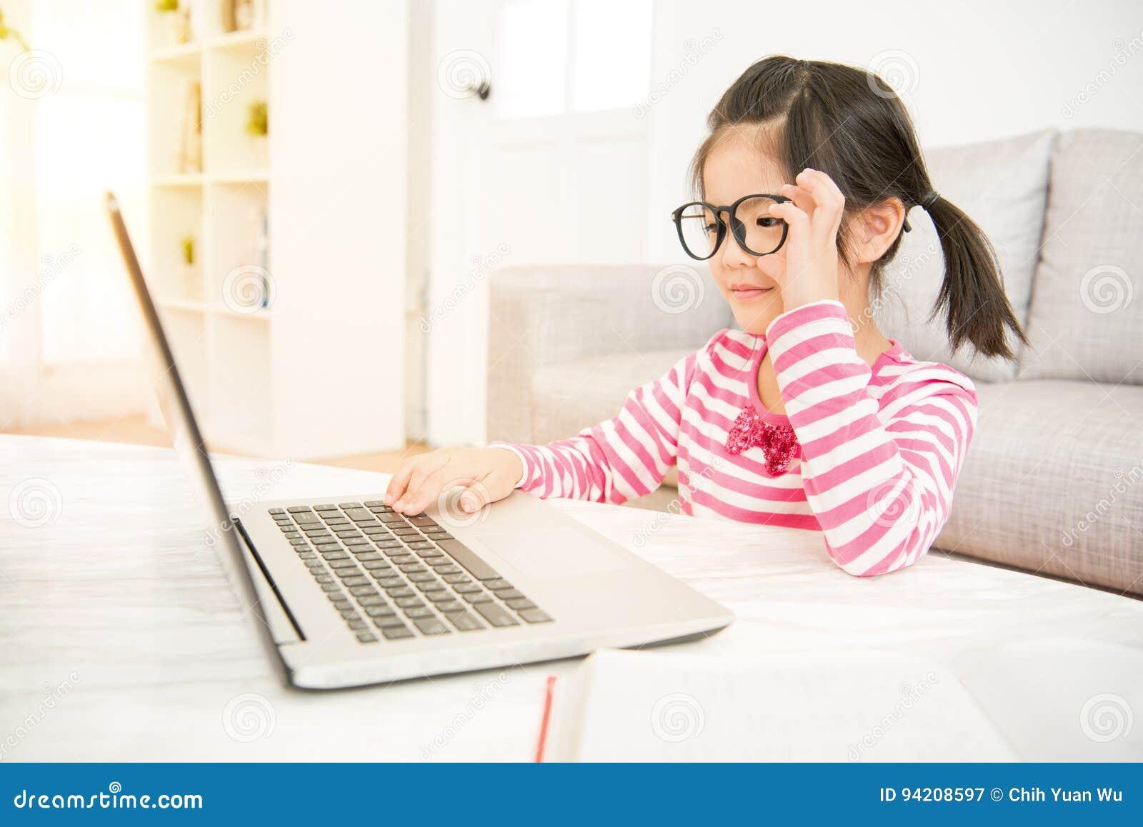 Dziewczyna jest ubranym dużych szkła używać jej laptop