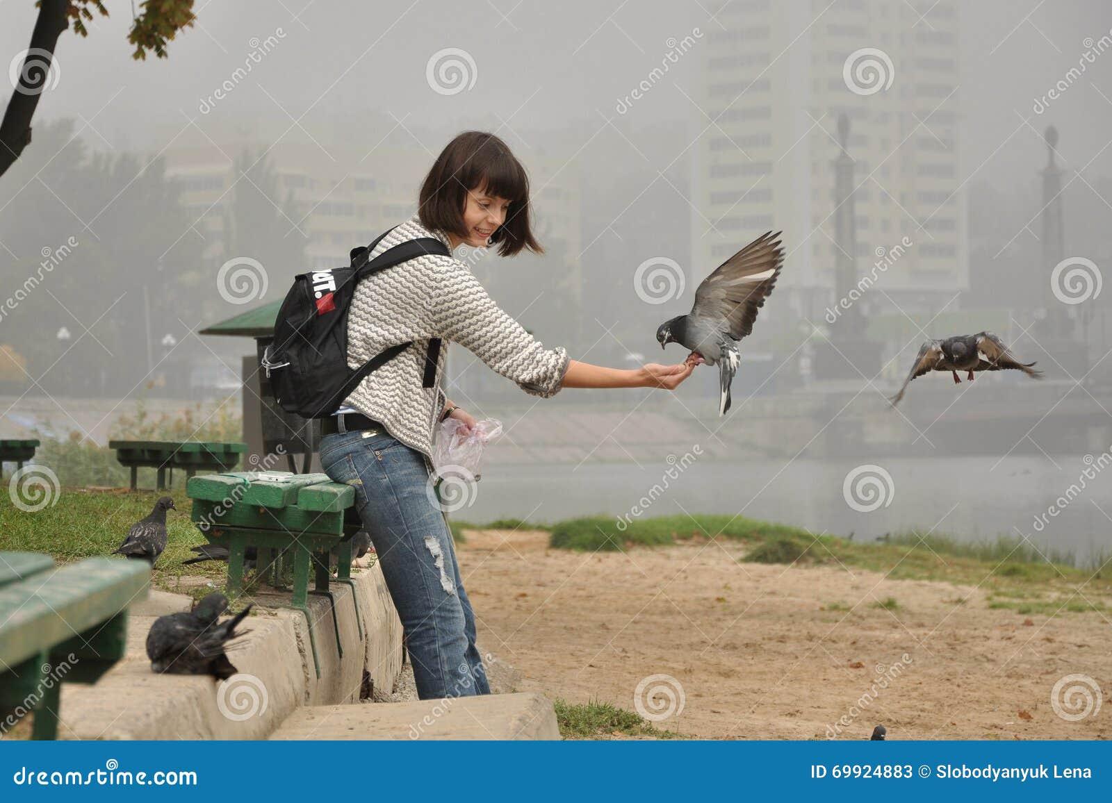 Dziewczyna karmi gołębie, ono uśmiecha się