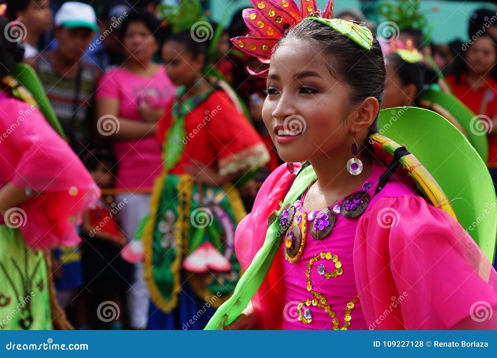 Dziewczyna karnawałowy tancerz w etnicznych kostiumach tanczy w zachwycie wzdłuż drogi