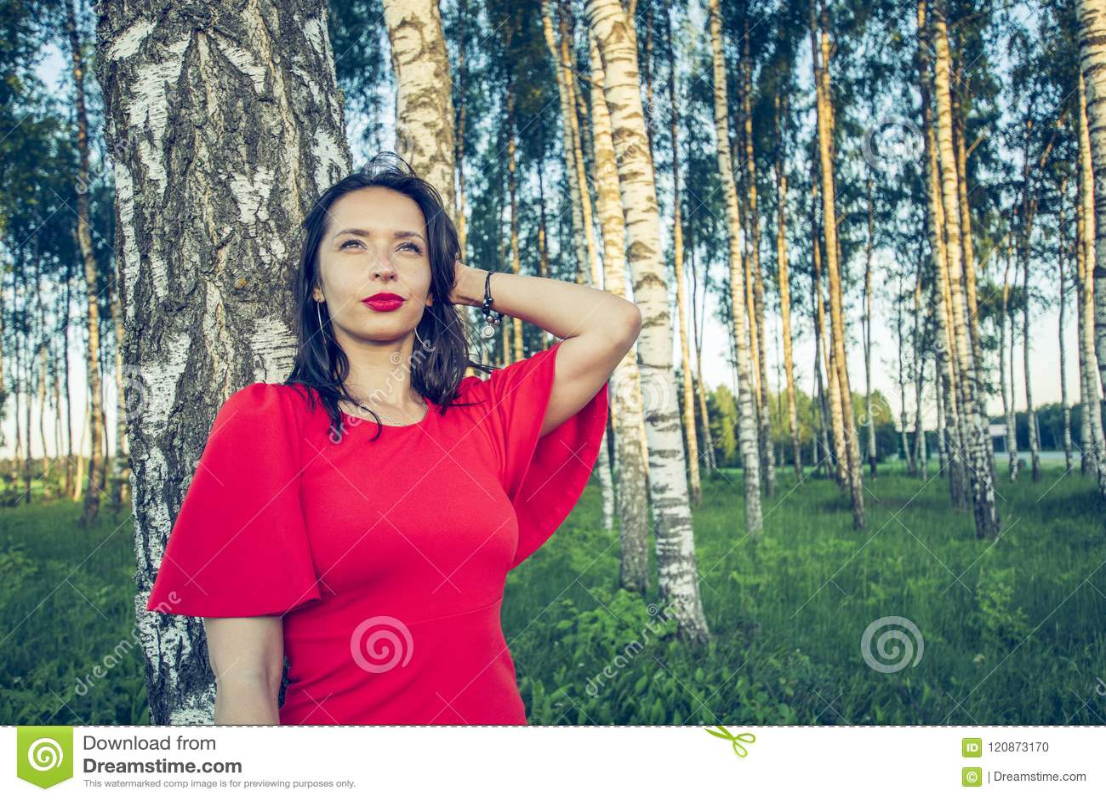 Dziewczyna marzy holdin blisko głowy z czerwonymi wargami w czerwieni sukni stoi w brzoza gaju jej ręka